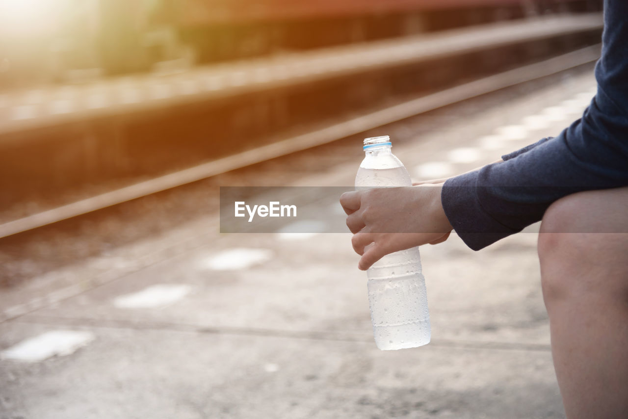 Midsection Of Person Holding Water Bottle At Railroad Station