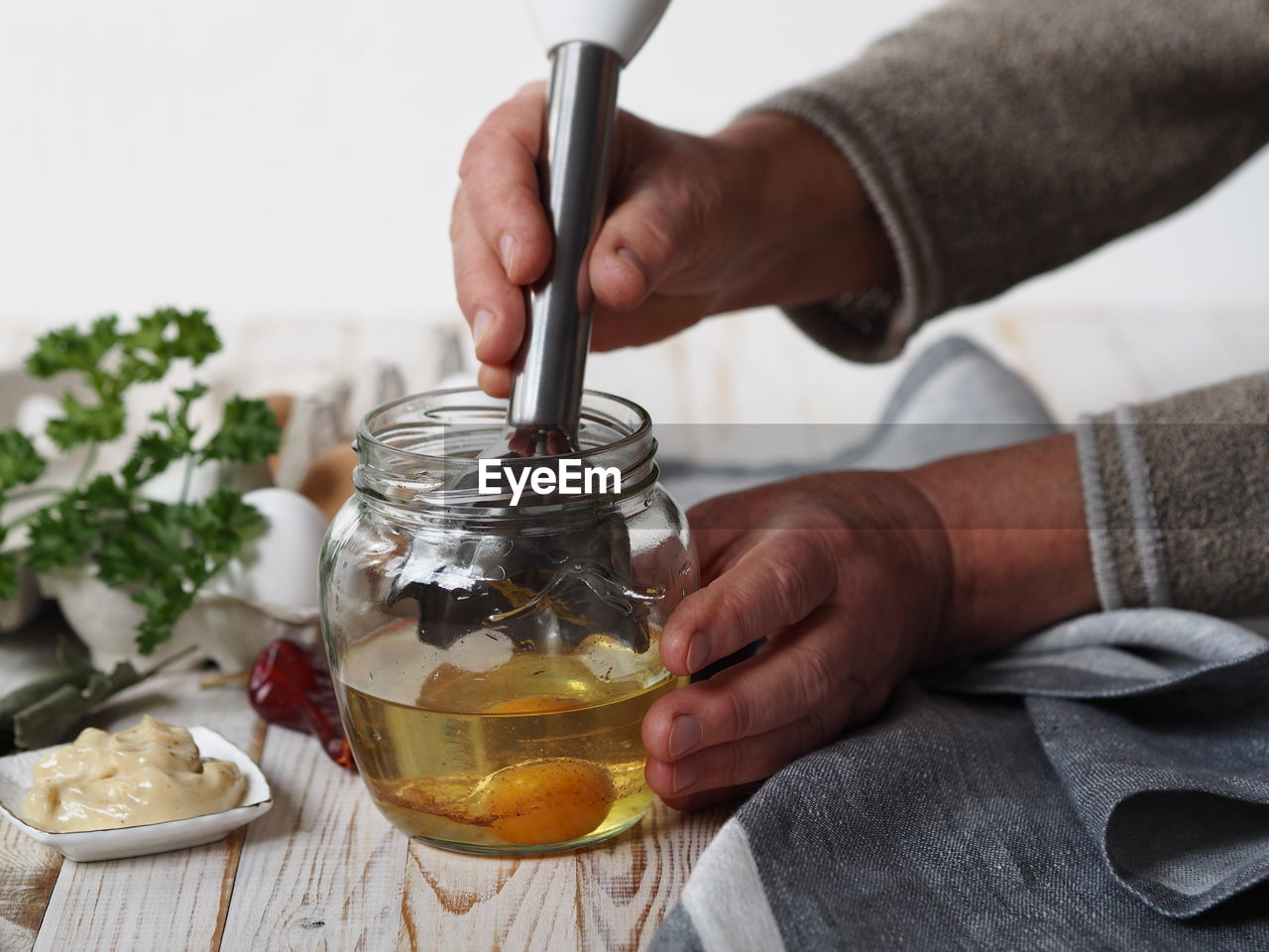 Midsection of person preparing food in glass jar on table