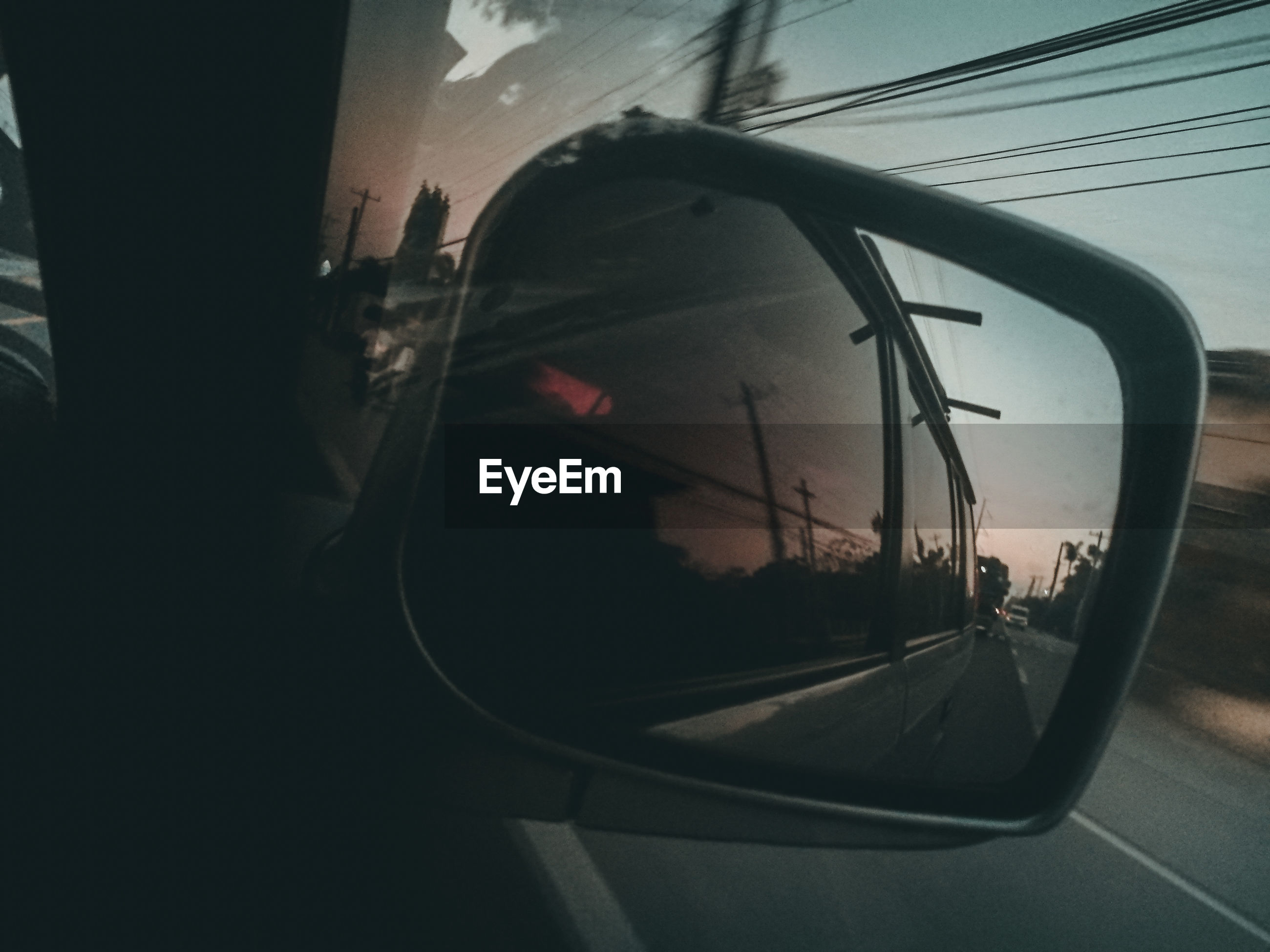 transportation, mode of transportation, land vehicle, glass - material, car, motor vehicle, reflection, side-view mirror, vehicle interior, travel, transparent, road, sky, window, nature, outdoors, journey, close-up, on the move, sunset, no people, vehicle mirror, road trip