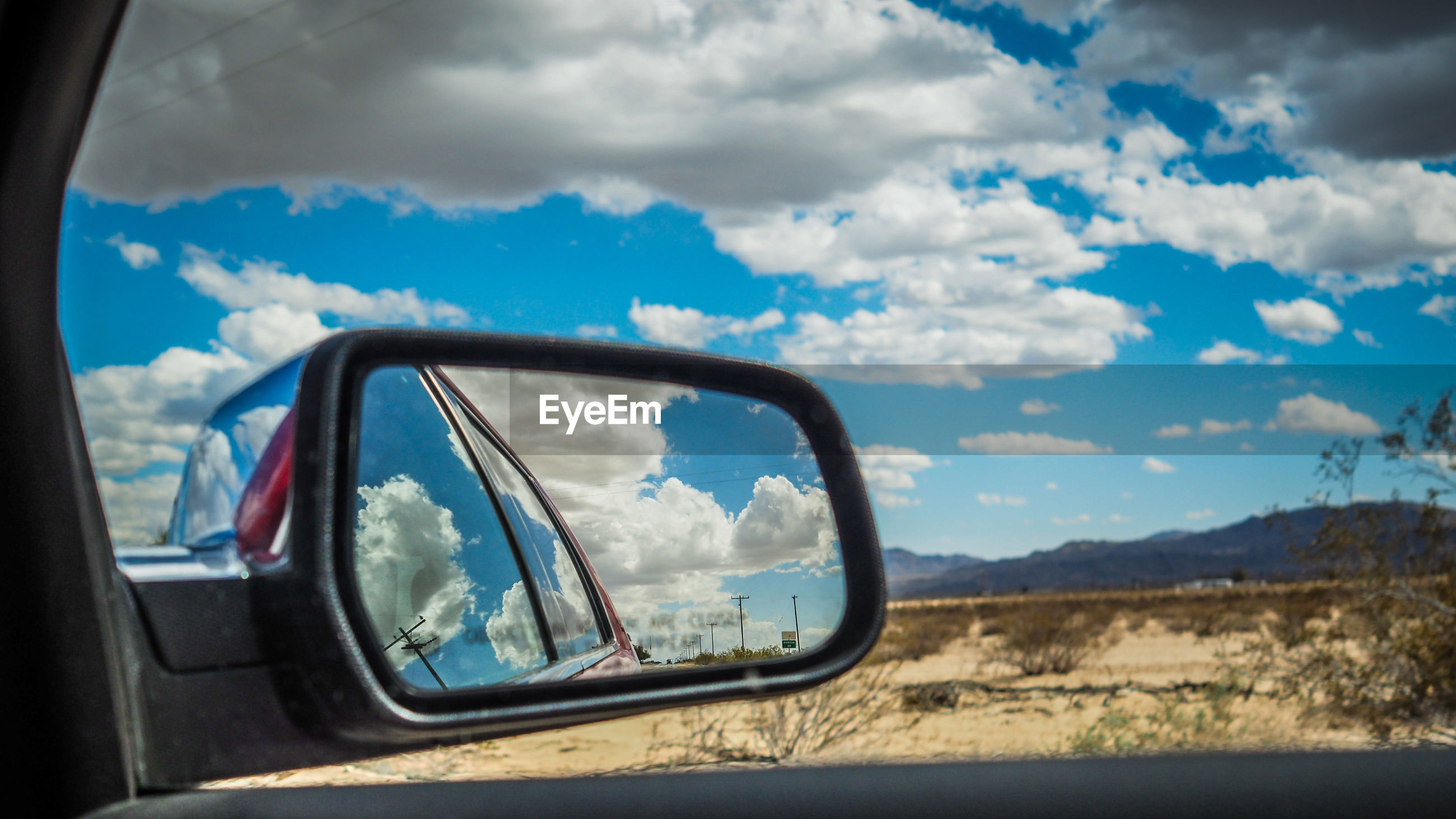 Reflection of car and sky on side-view mirror
