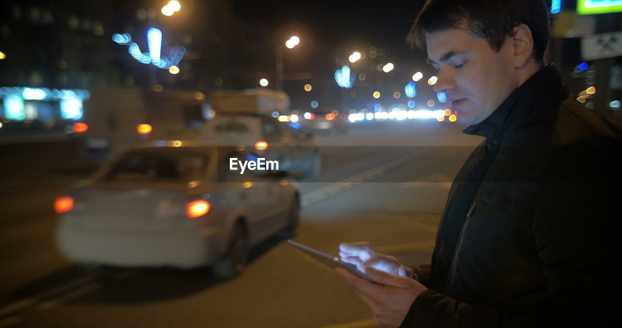 BLURRED MOTION OF MAN HOLDING ILLUMINATED STREET AT NIGHT