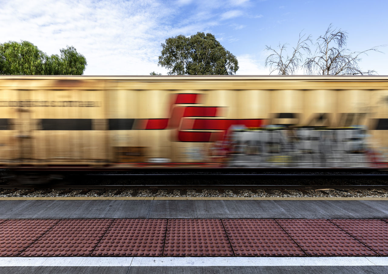 motion, rail transportation, public transportation, blurred motion, mode of transportation, train, transportation, train - vehicle, speed, tree, track, red, railroad track, no people, on the move, plant, day, architecture, nature, land vehicle, outdoors