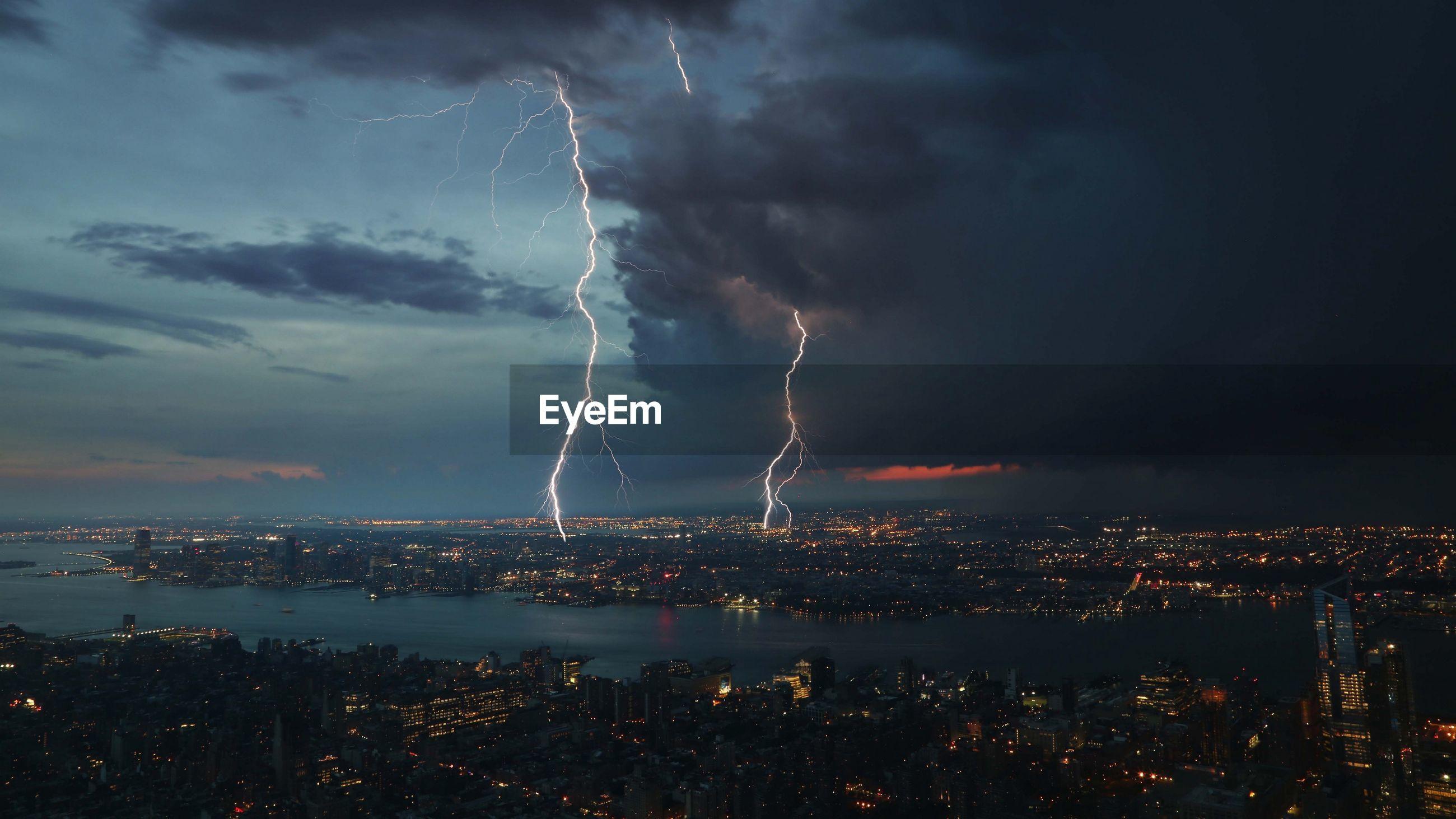 LIGHTNING OVER ILLUMINATED CITYSCAPE AGAINST SKY