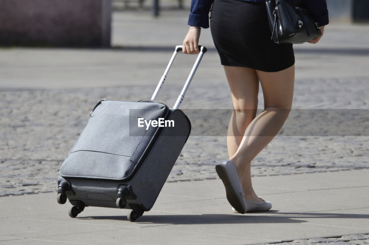 Low section of woman with luggage walking on footpath