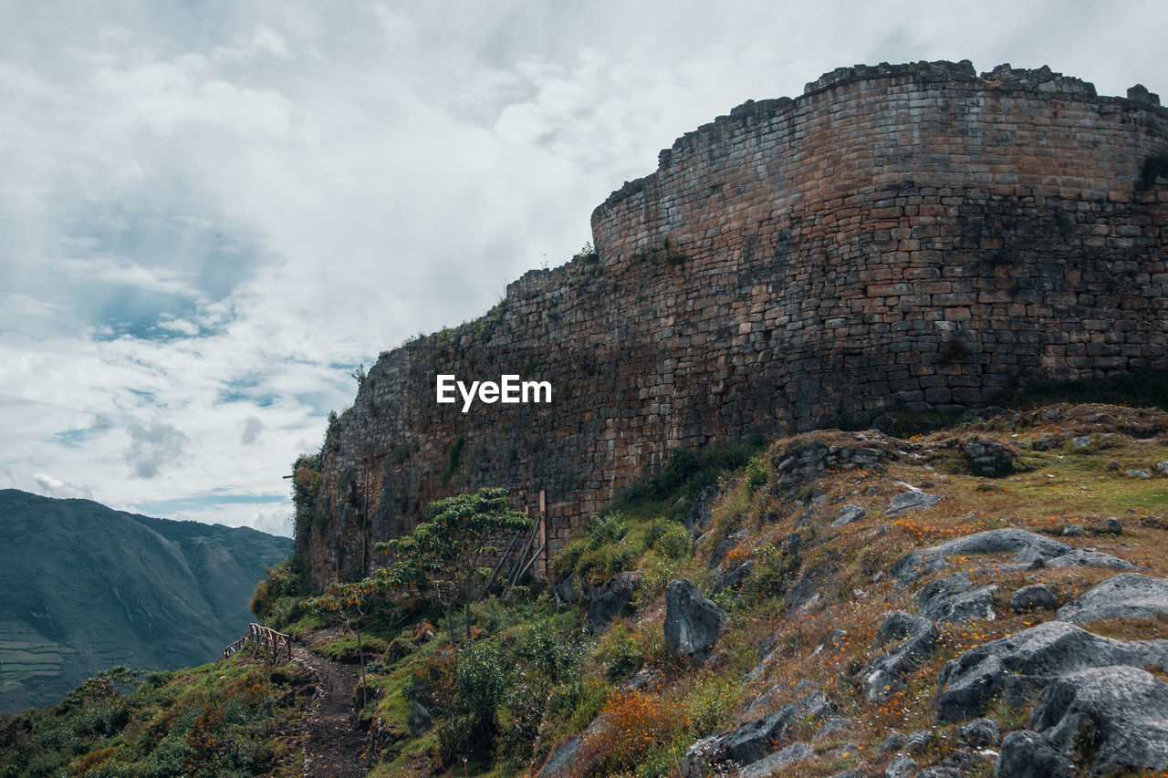 mountain, sky, cloud - sky, nature, scenics - nature, day, rock, solid, rock - object, beauty in nature, tranquility, no people, tranquil scene, non-urban scene, low angle view, rock formation, mountain range, travel destinations, outdoors, cliff, formation, ancient civilization, mountain peak