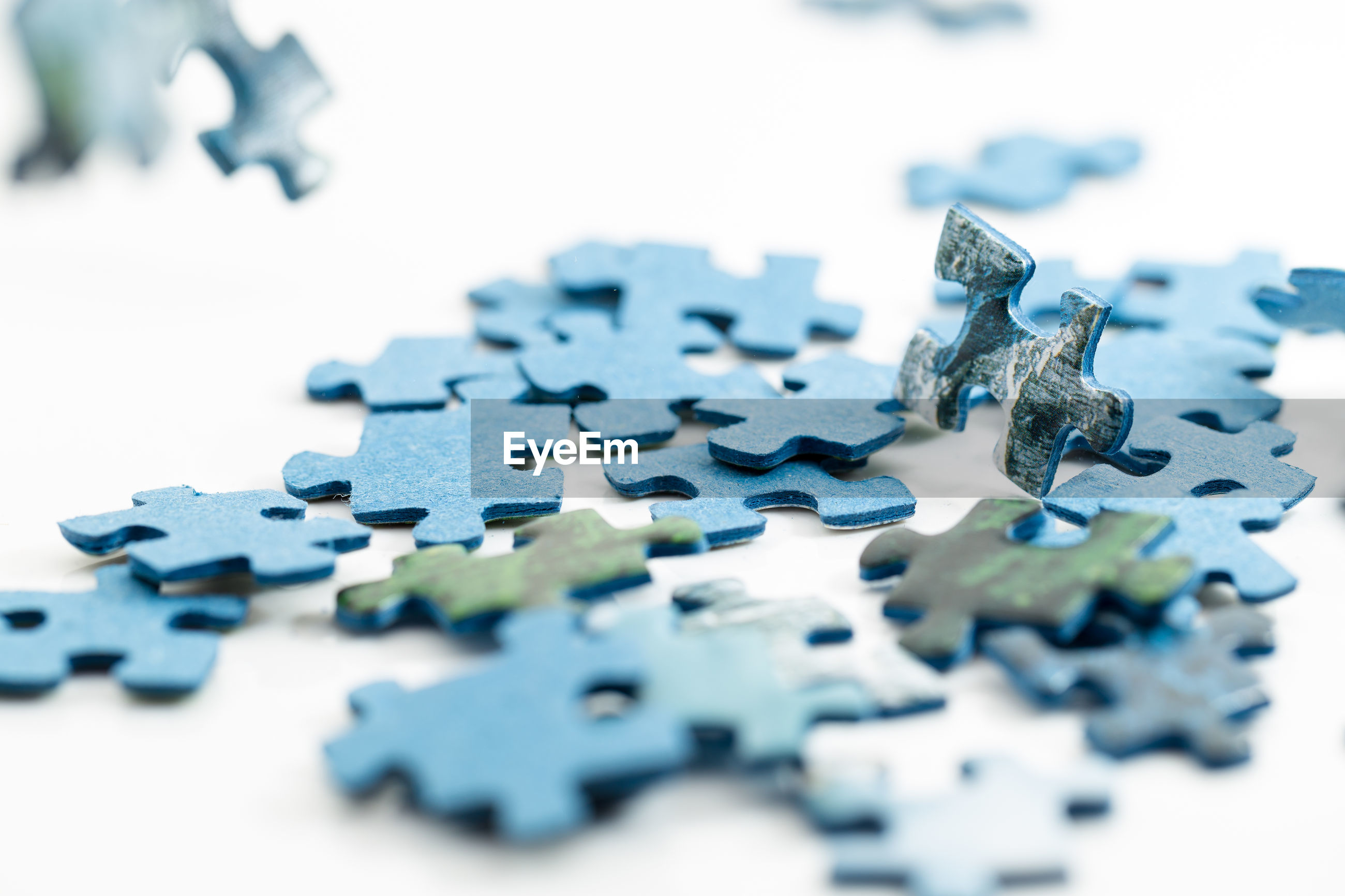 Close-up of blue jigsaw puzzle pieces against white background