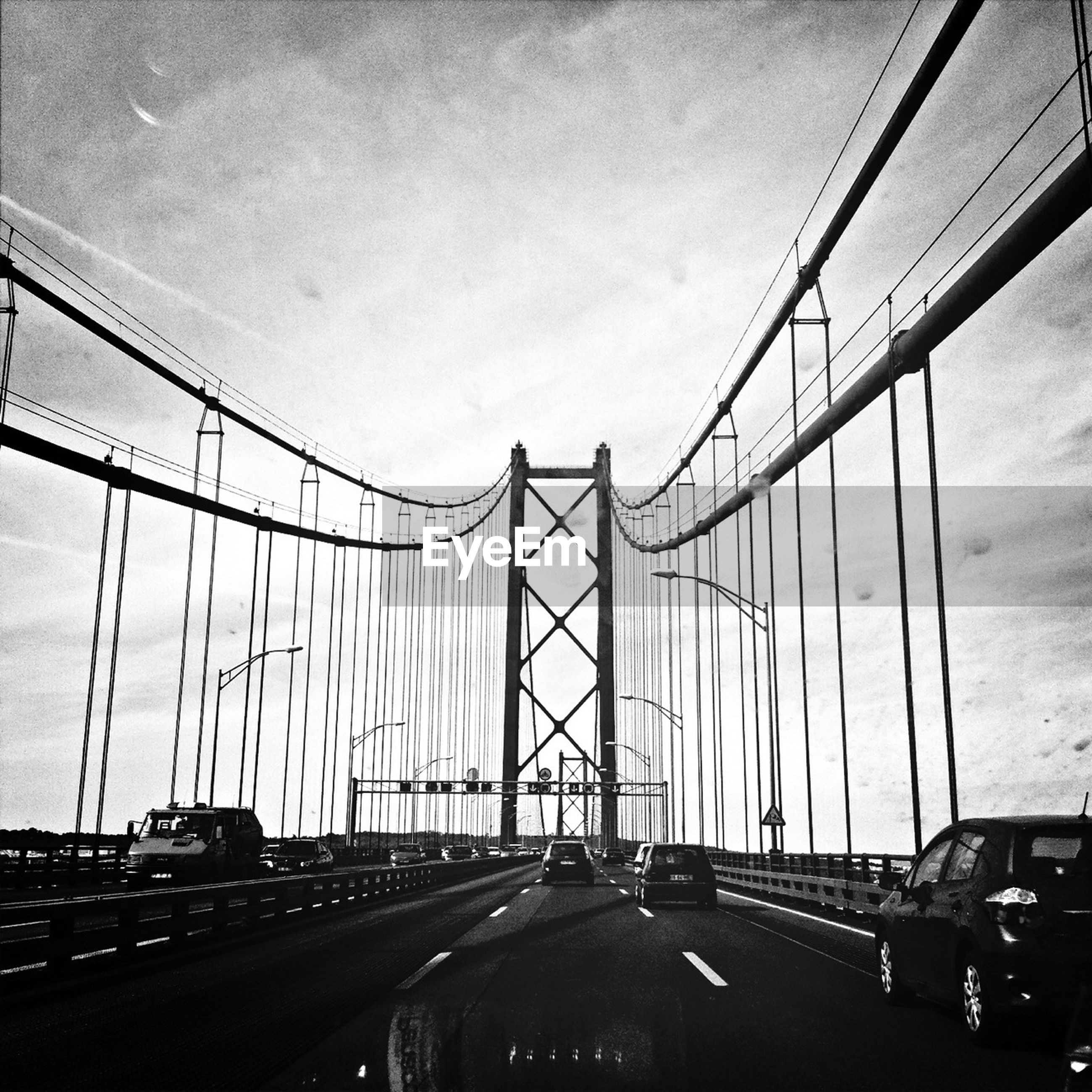 transportation, car, connection, road, mode of transport, land vehicle, sky, bridge - man made structure, the way forward, road marking, engineering, built structure, diminishing perspective, highway, architecture, on the move, suspension bridge, cloud - sky, travel, low angle view