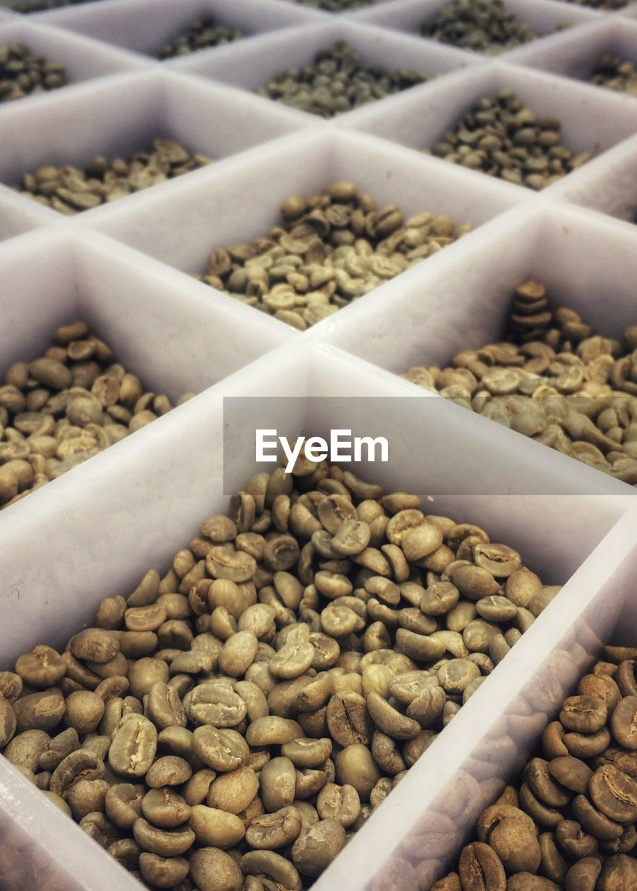 Close-Up Of Raw Coffee Beans In Containers For Sale At Market