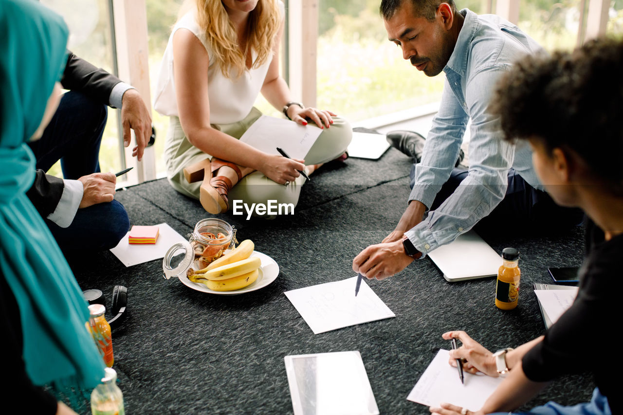 HIGH ANGLE VIEW OF PEOPLE SITTING ON TABLE AT HOME