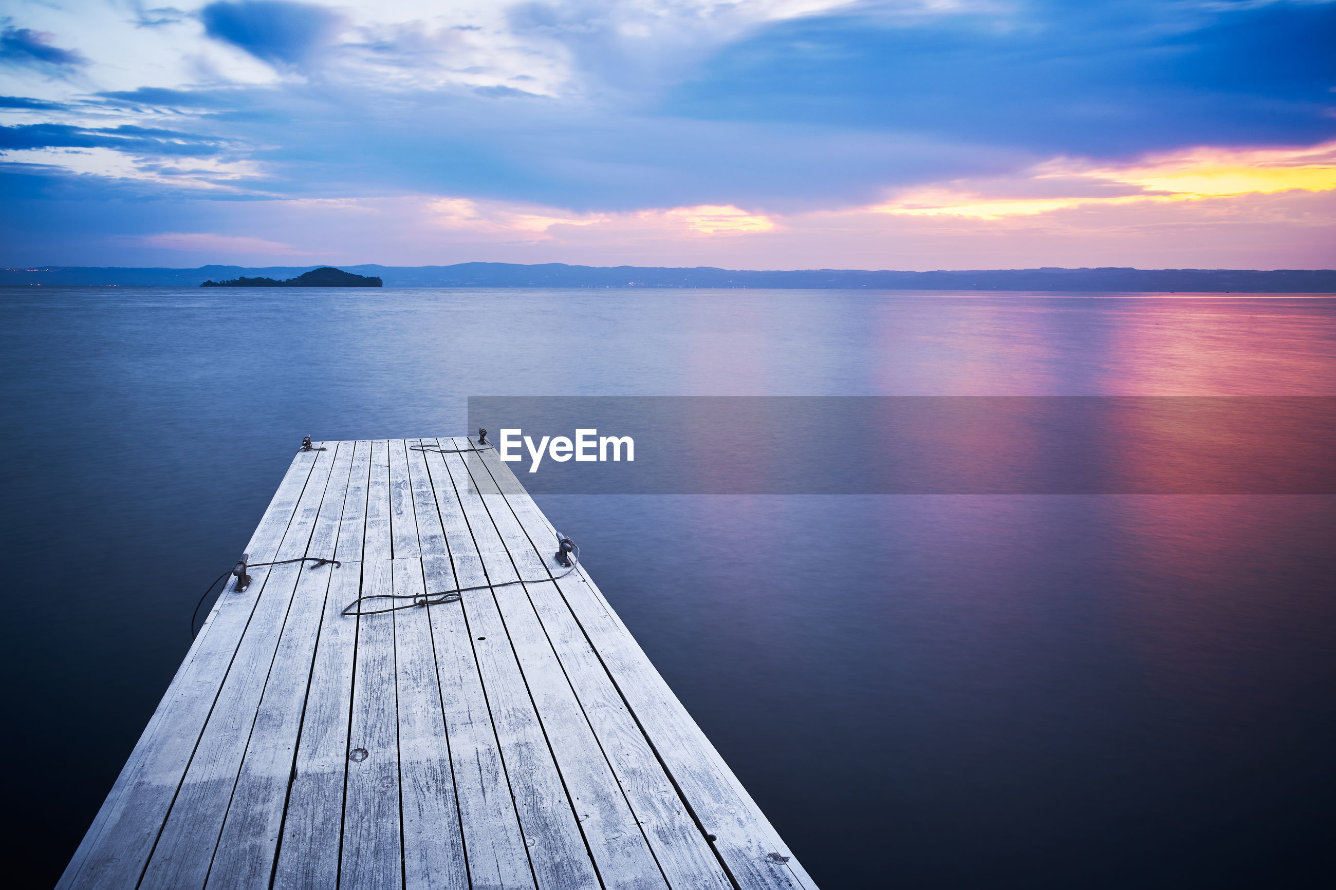 Wooden pier on bolsena lake at sunrise dawn, on water, long exposure and bientina island