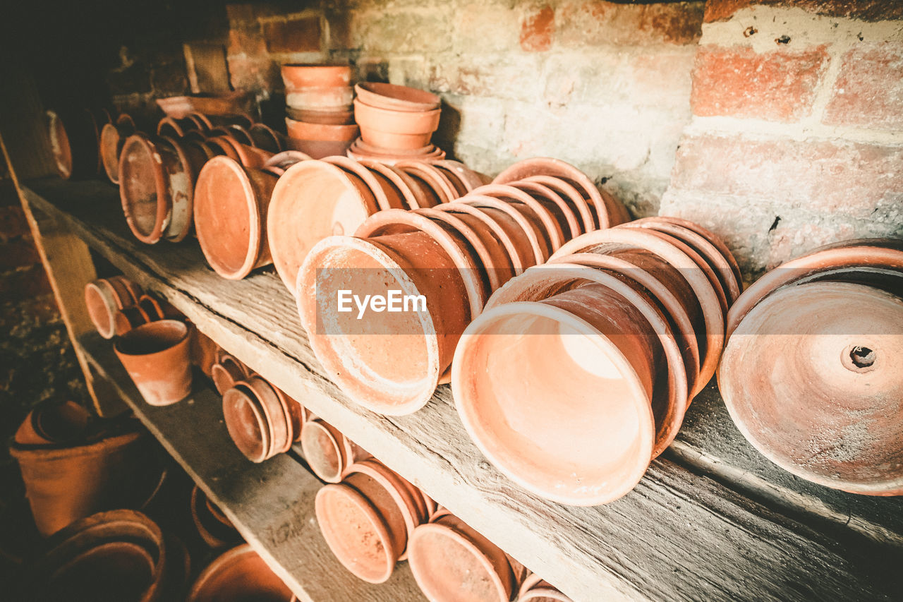 still life, pottery, large group of objects, earthenware, ceramics, indoors, no people, container, clay, craft, art and craft, choice, brown, variation, business, wood - material, small business, stack, close-up, high angle view, crockery