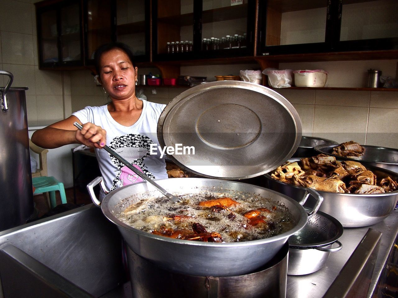 kitchen, food, food and drink, indoors, kitchen utensil, domestic room, one person, domestic kitchen, preparation, household equipment, home, preparing food, holding, stove, standing, real people, appliance, cooking pan, occupation, chef