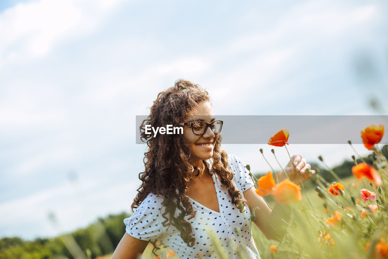 Smiling Woman Looking At Flowers Against Sky