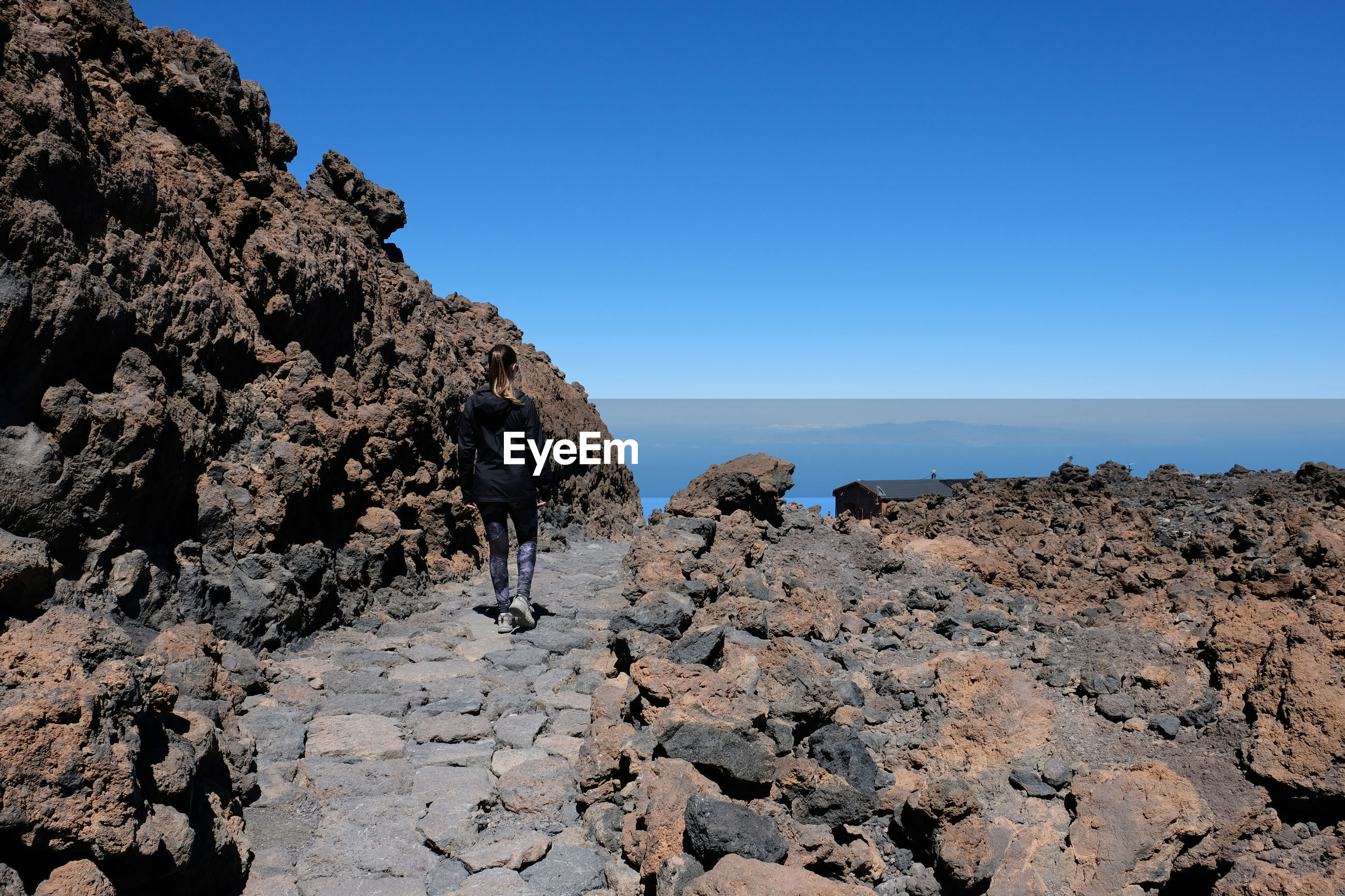 Rear view of woman walking on footpath by rock formation against clear blue sky