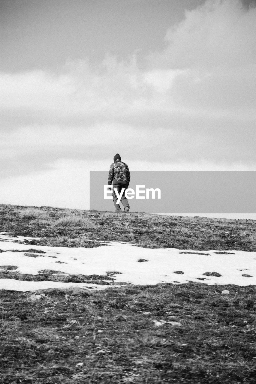 Scenic view of person on snow covered field against cloudy sky