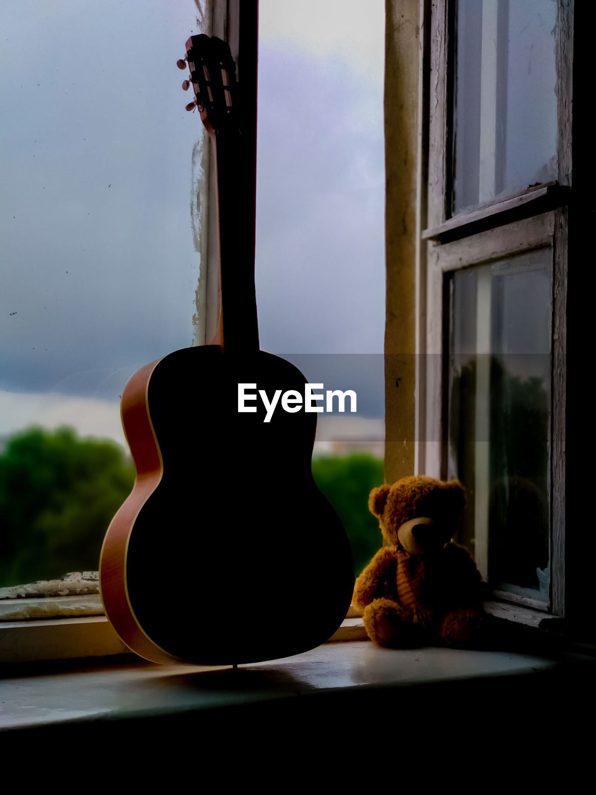 Close-up of stuffed toy and guitar by window at home
