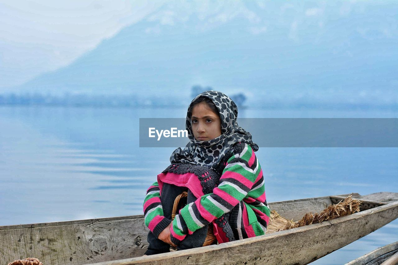 Young woman wearing warm clothing looking away on rowboat in lake
