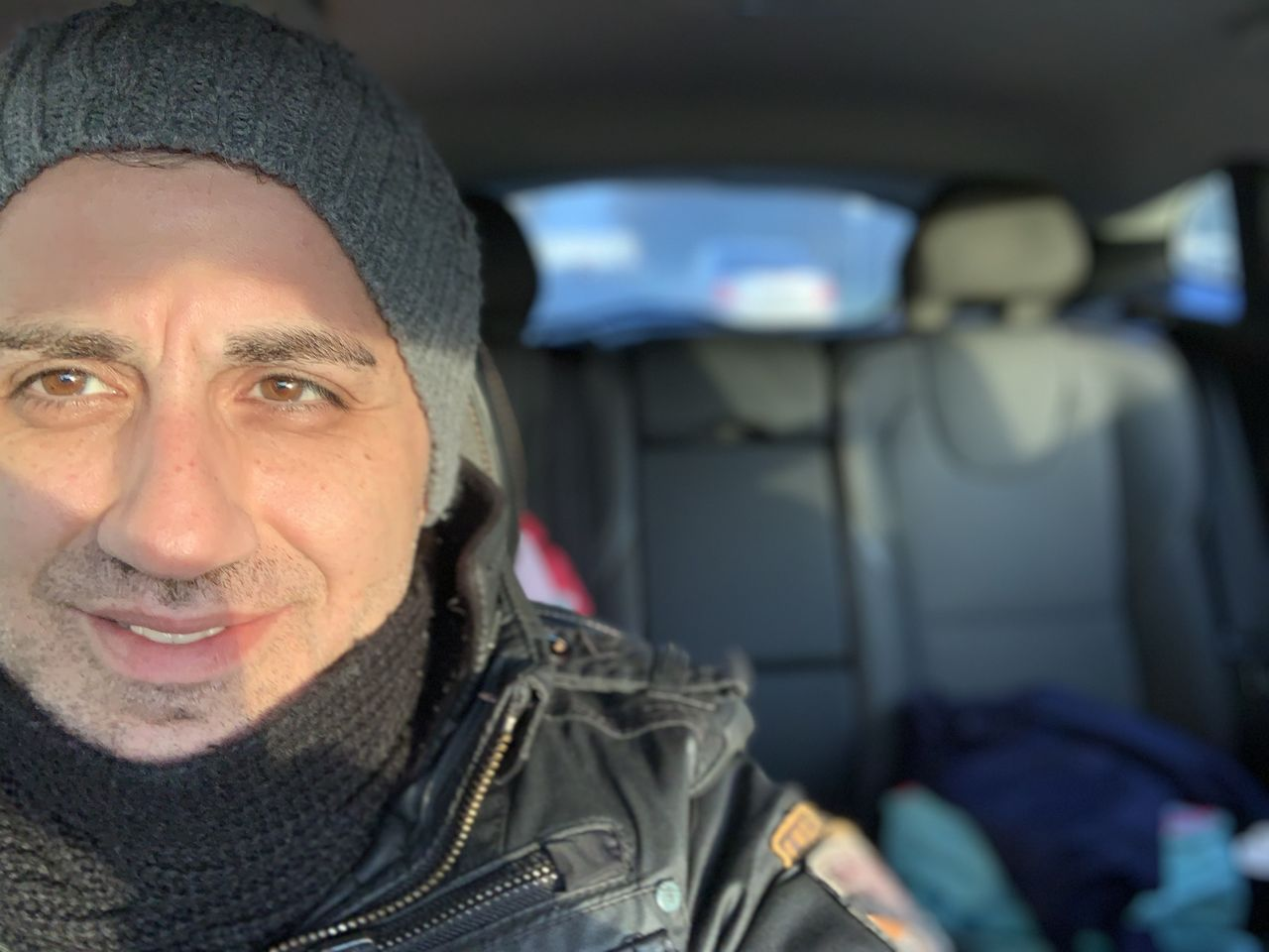 car, motor vehicle, portrait, mode of transportation, transportation, clothing, looking at camera, vehicle interior, land vehicle, winter, front view, people, warm clothing, car interior, travel, men, mid adult, headshot, scarf