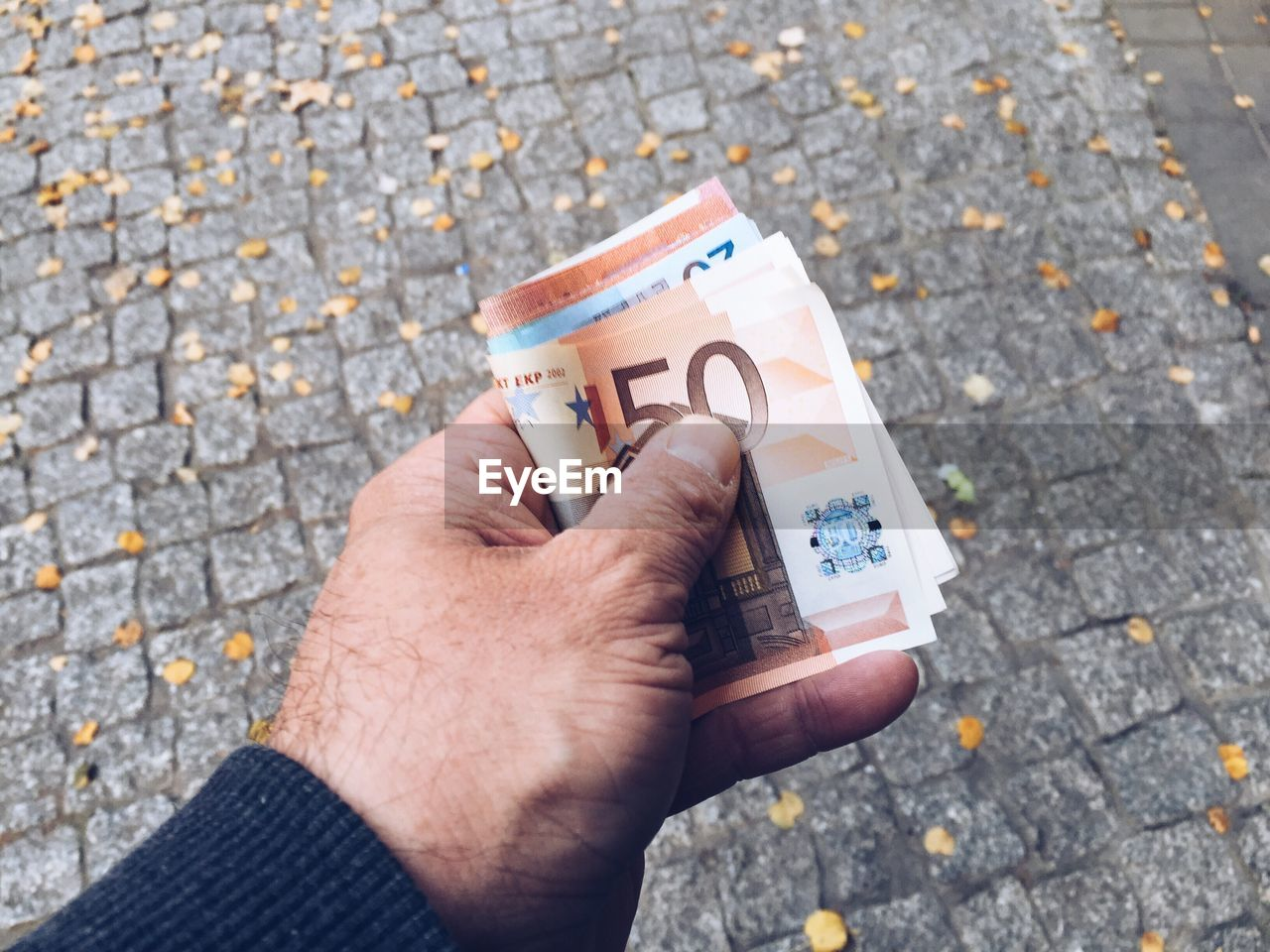 Cropped hand holding paper currency over street