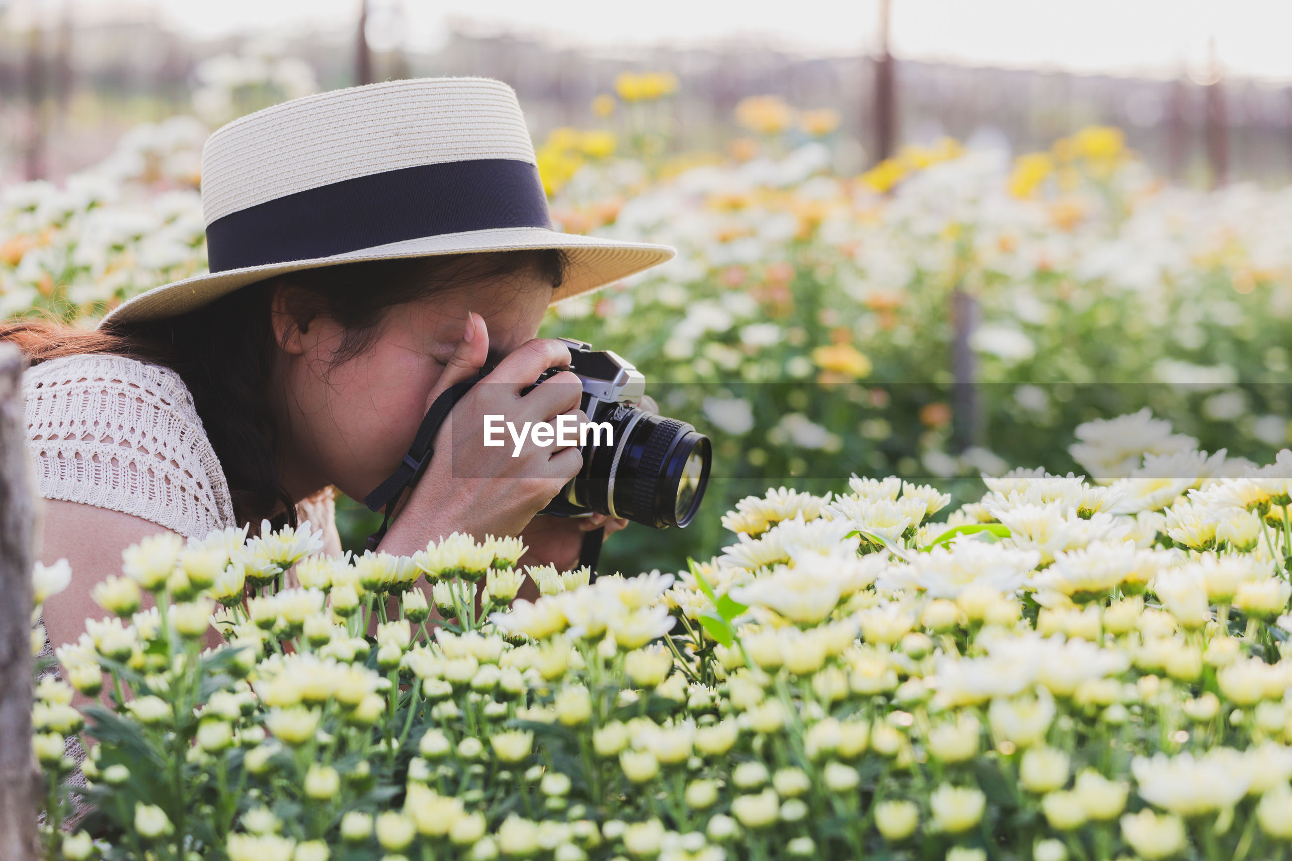 Woman photographing flowers with camera
