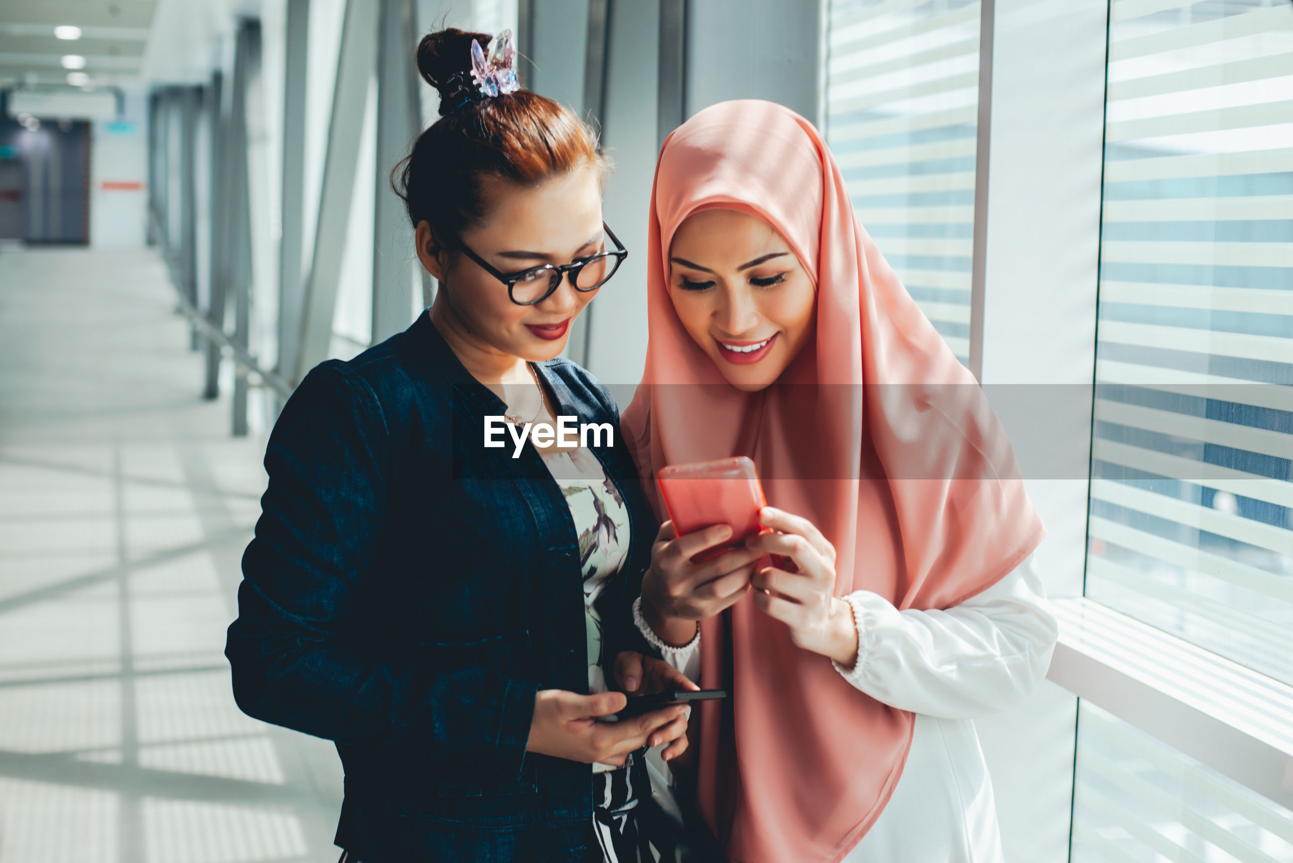 Women with smart phone by window