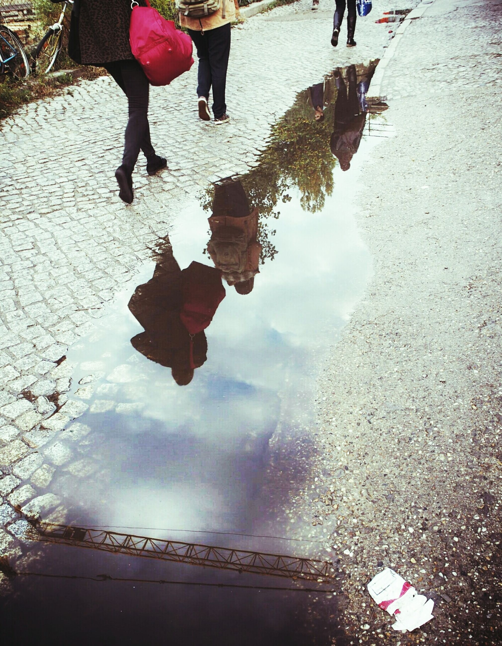 Commuters reflecting in puddle