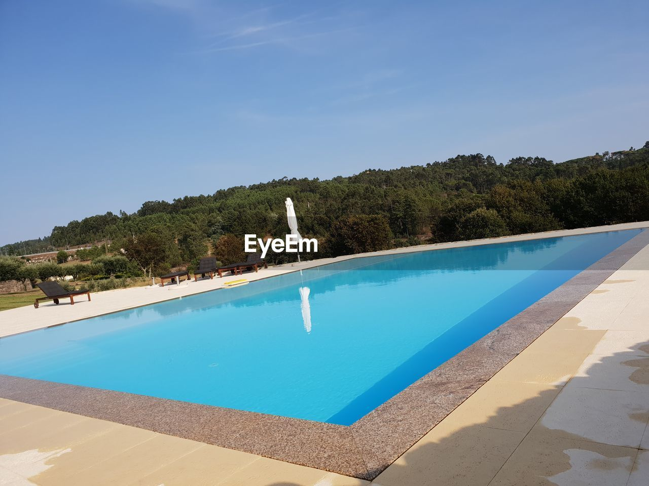 HIGH ANGLE VIEW OF SWIMMING POOL BY TREES AGAINST SKY