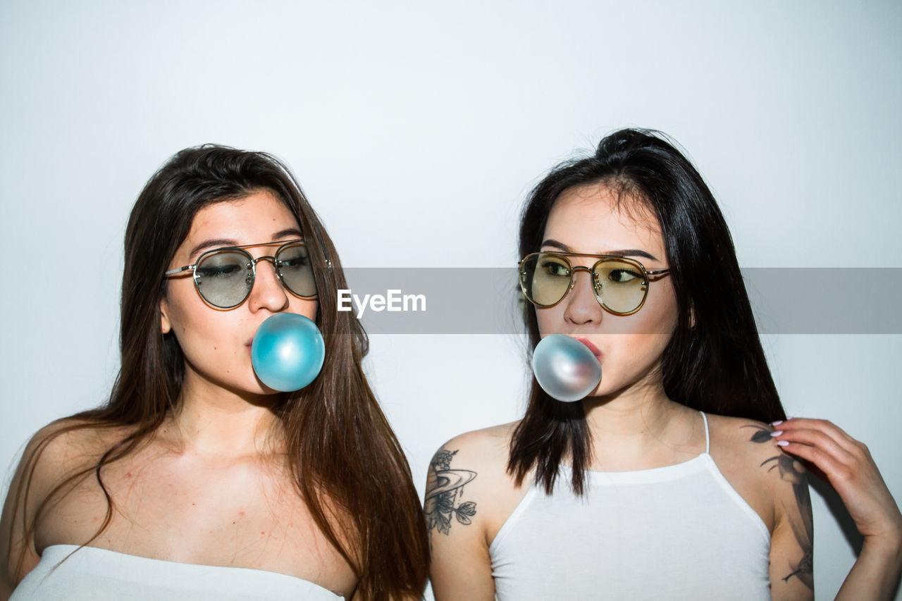 Portrait Of Young Women Blowing Bubble Gum