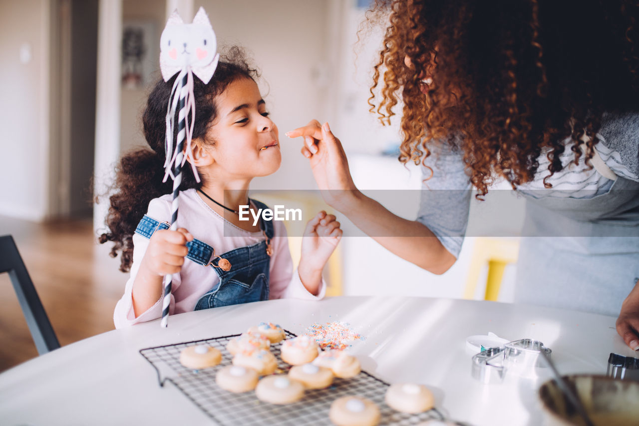 Mother feeding cookies to daughter at home