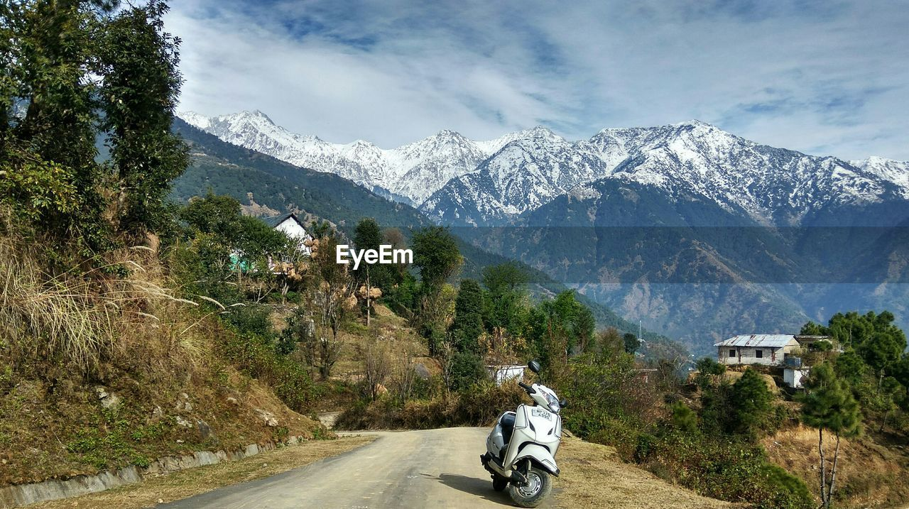 mountain, transportation, road, motorcycle, mountain range, mode of transport, nature, land vehicle, adventure, day, sky, outdoors, landscape, real people, beauty in nature, tree, one person, people
