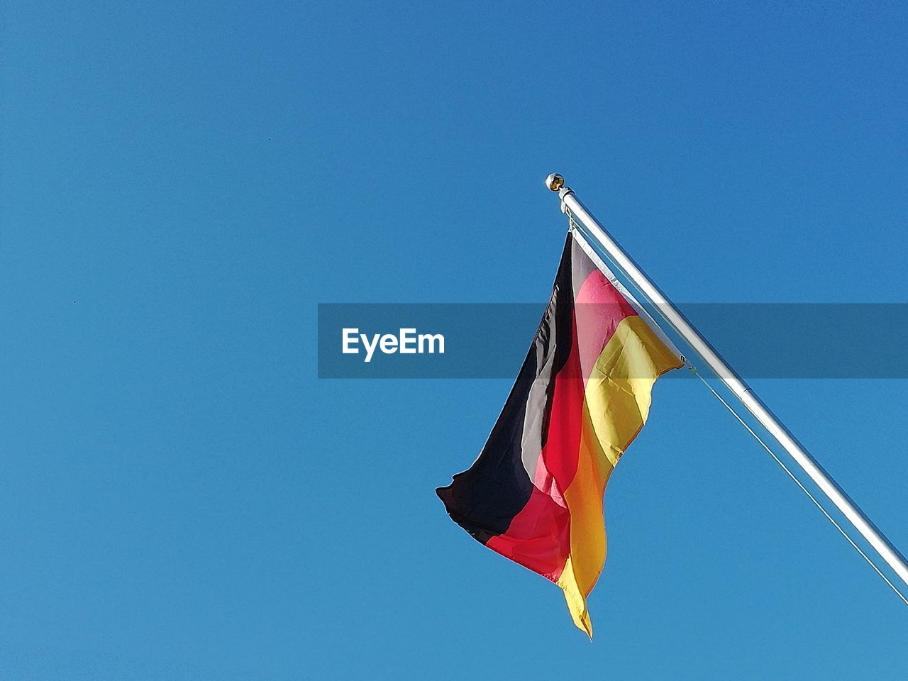 Low angle view of german flag waving against clear blue sky