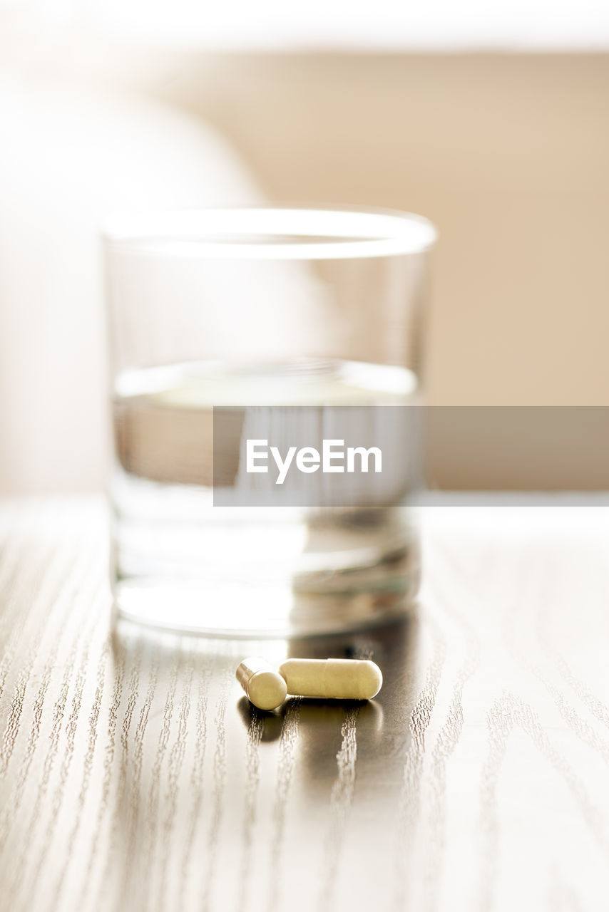 table, indoors, still life, close-up, selective focus, no people, focus on foreground, food and drink, pill, wood - material, container, jar, dose, healthcare and medicine, food, drink, white color, medicine, glass - material, refreshment
