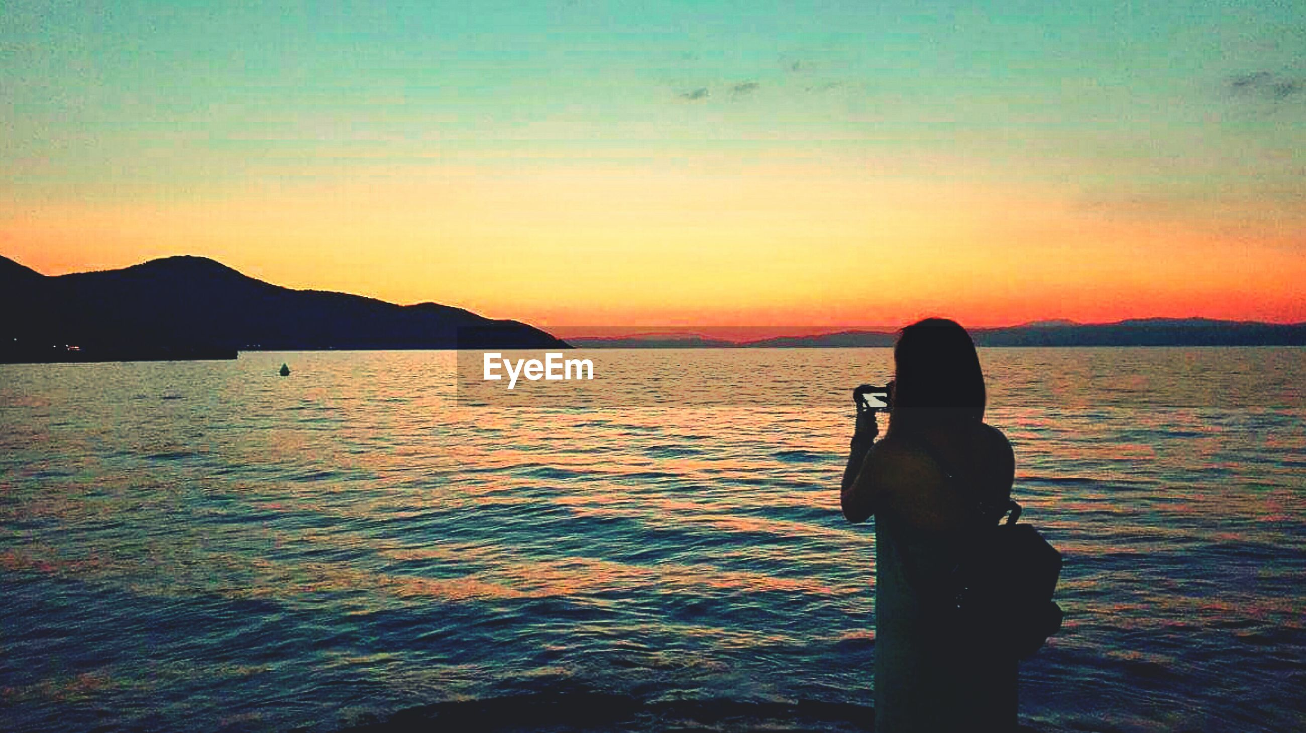 Rear view of silhouette young woman photographing with mobile phone while standing in sea against sky during sunset
