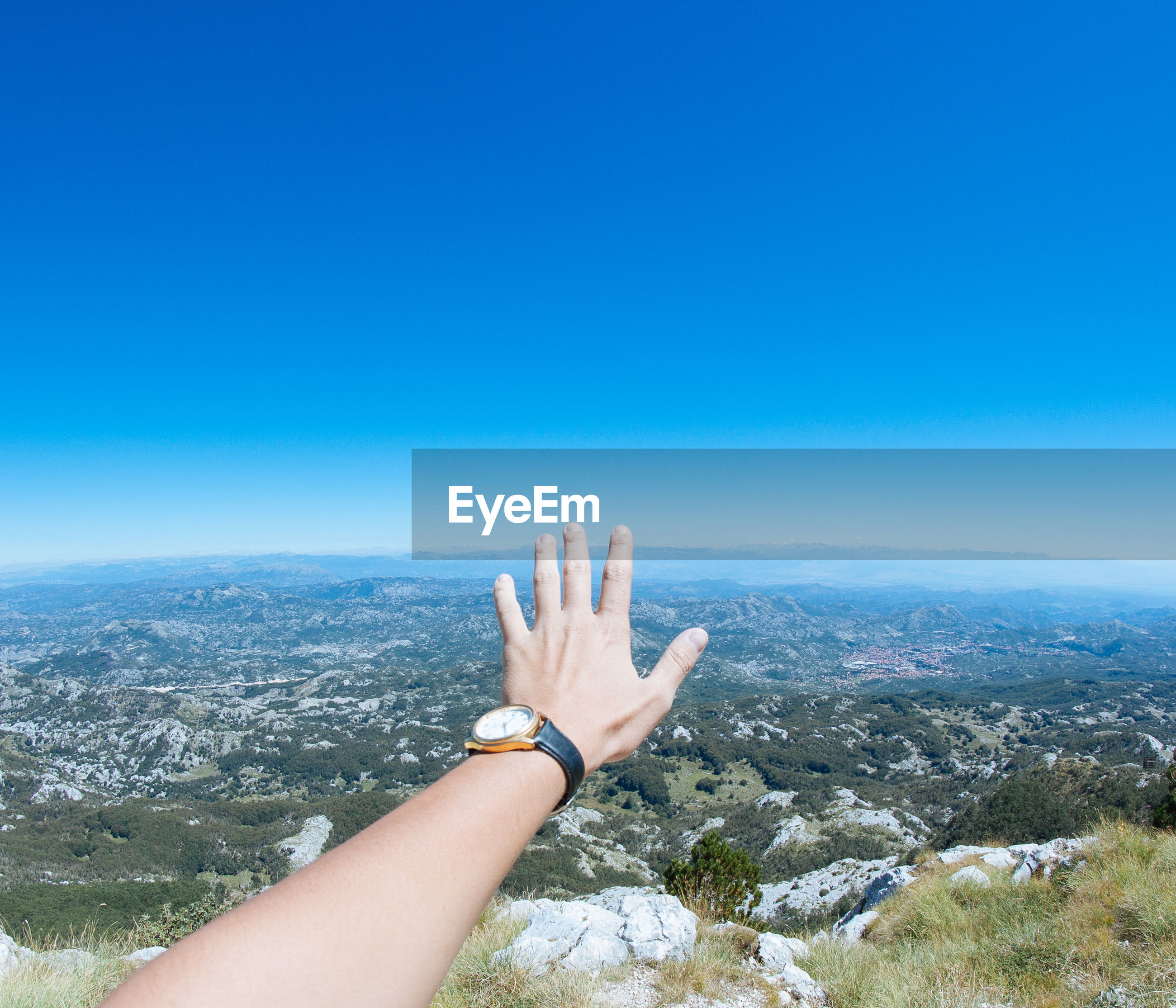 Cropped hand of woman against clear blue sky