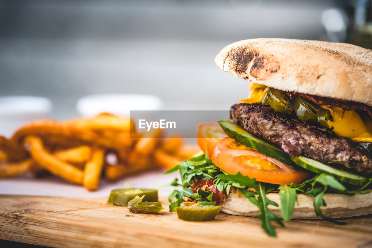 vegetable, food and drink, food, sandwich, fast food, burger, ready-to-eat, unhealthy eating, freshness, meat, bread, table, hamburger, indoors, close-up, still life, wood - material, tomato, selective focus, no people, bun, meal, snack