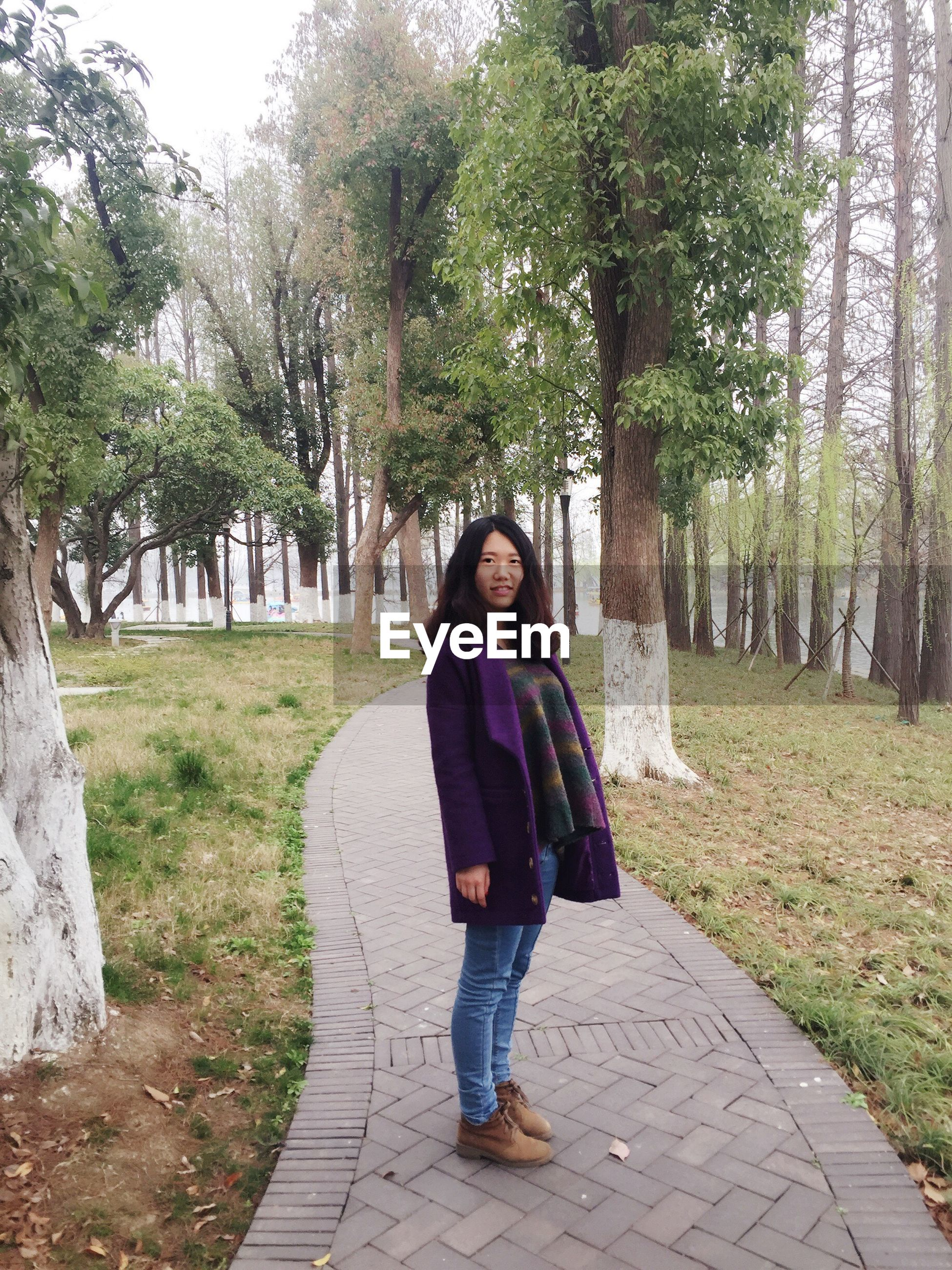 tree, lifestyles, casual clothing, full length, person, leisure activity, looking at camera, young adult, portrait, footpath, front view, park - man made space, young women, grass, smiling, the way forward, standing, day