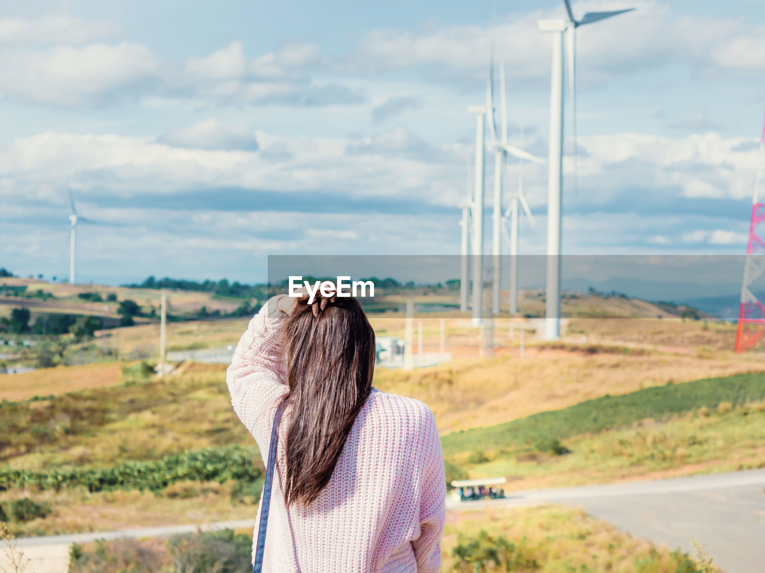 Rear view of woman standing against windmills on landscape