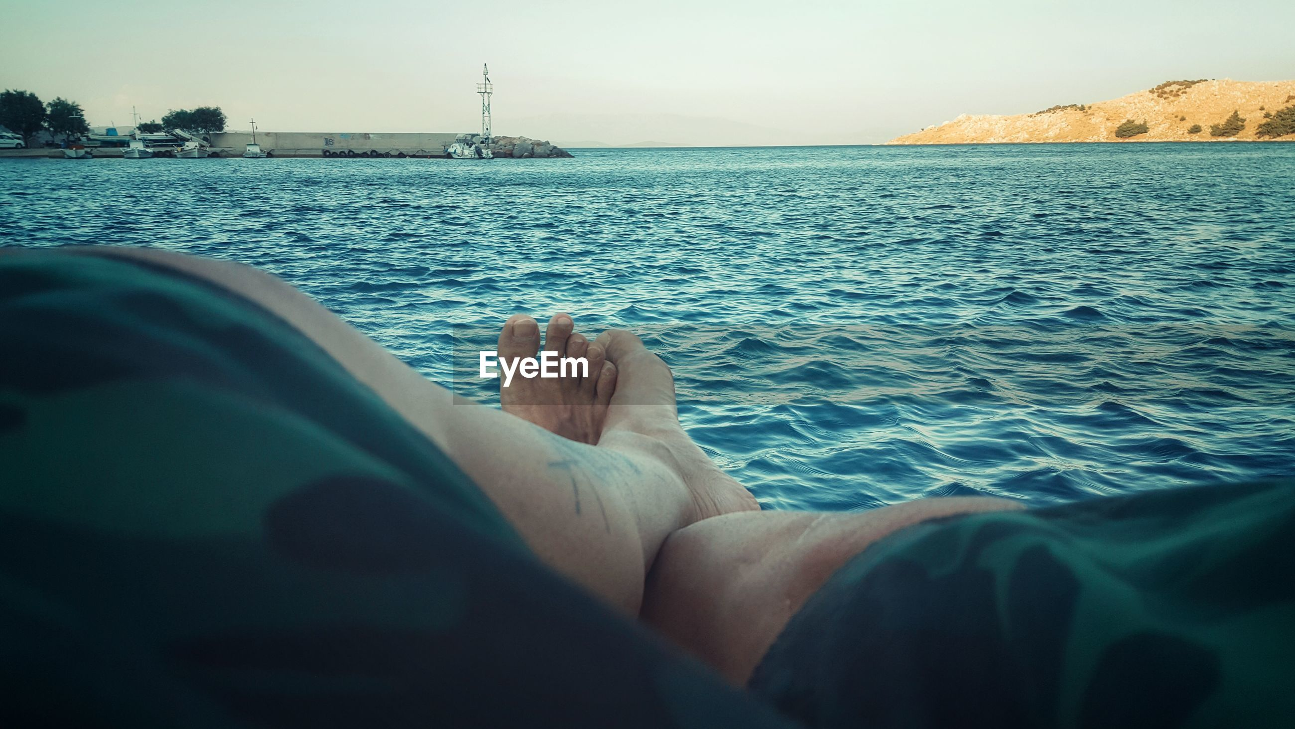 Low section of man resting by sea against clear sky