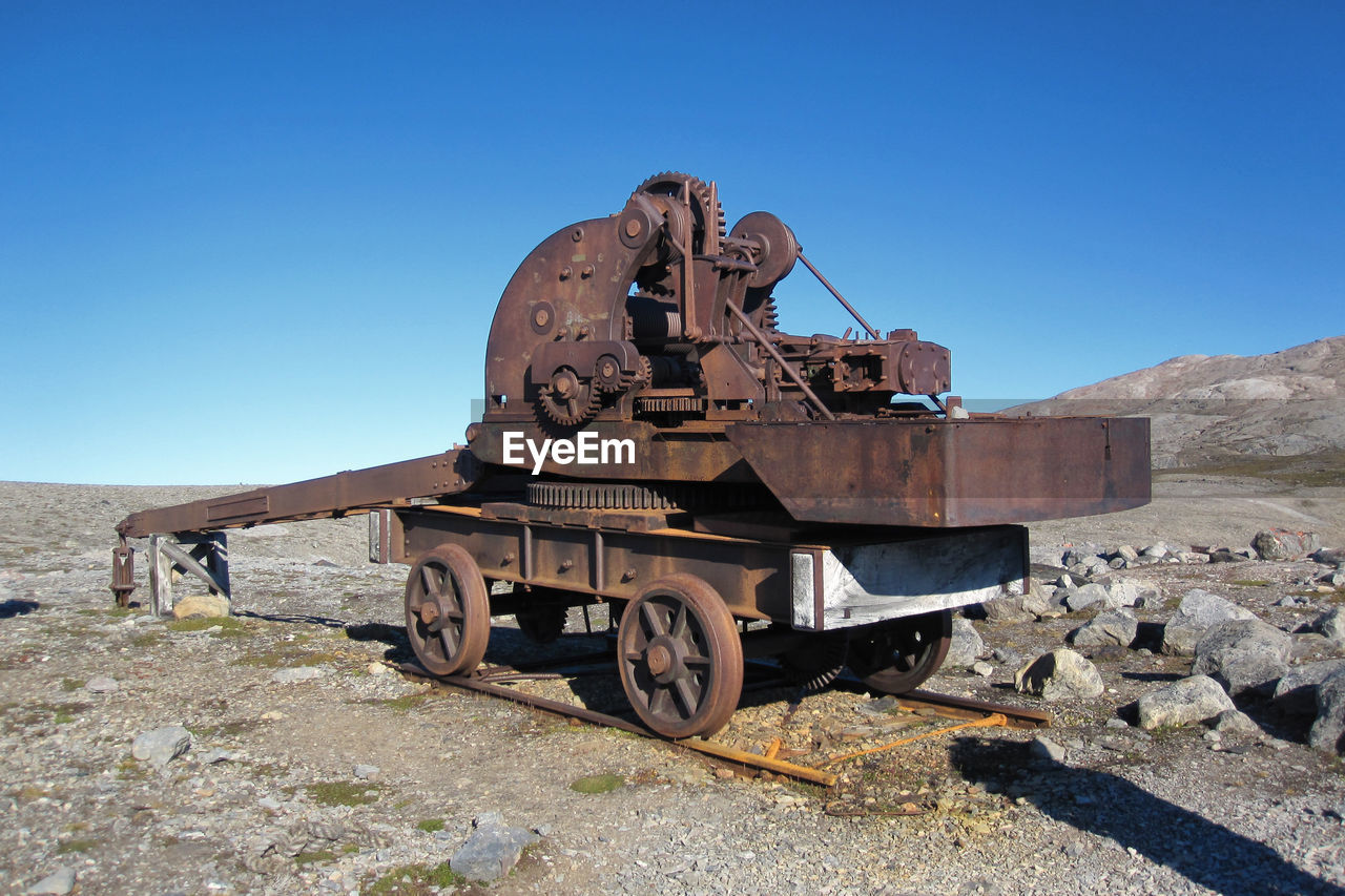 sky, clear sky, transportation, day, nature, sunlight, mode of transportation, rail transportation, land vehicle, travel, abandoned, environment, copy space, outdoors, damaged, no people, land, blue, old, stationary, track, deterioration, arid climate