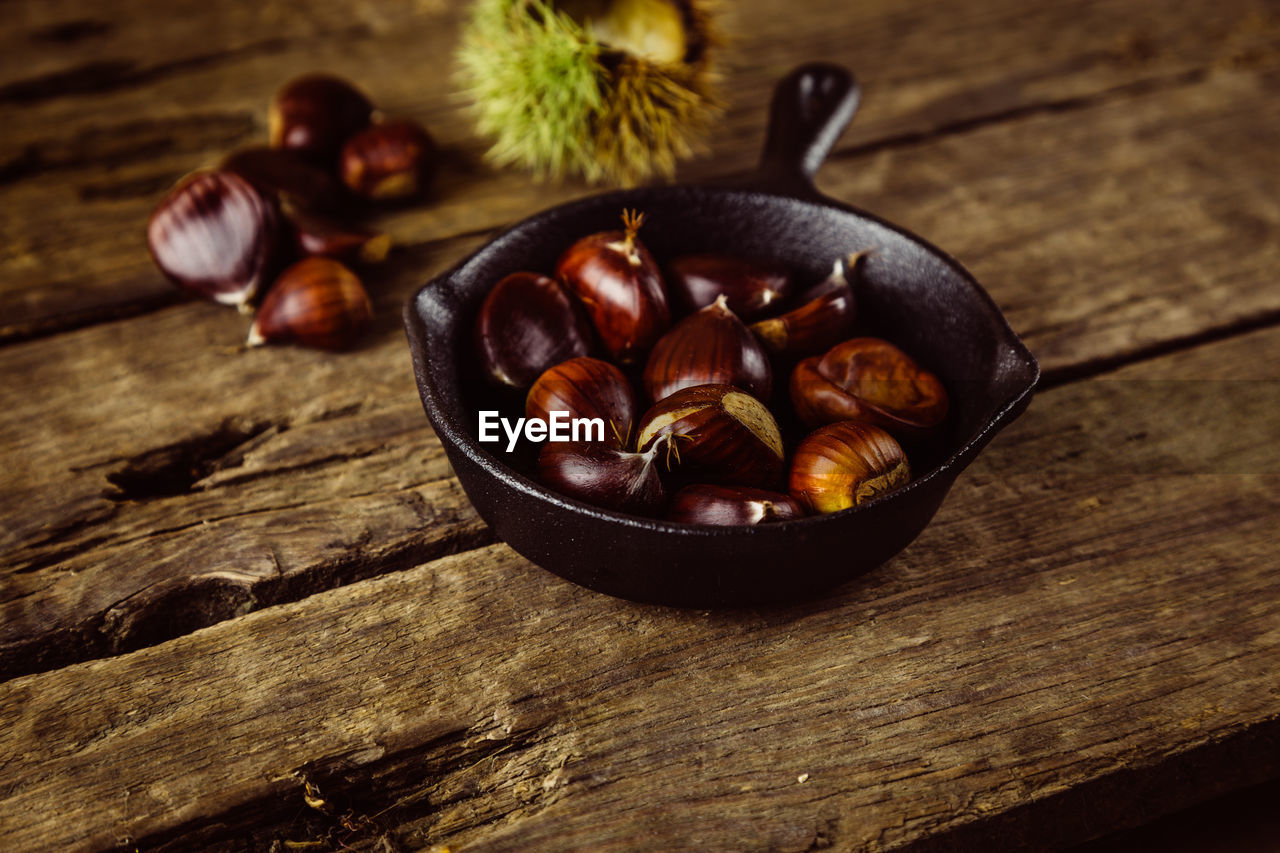 food and drink, food, wood - material, freshness, table, healthy eating, still life, wellbeing, no people, close-up, chestnut, indoors, high angle view, chestnut - food, nut - food, bowl, focus on foreground, ingredient, brown, nut