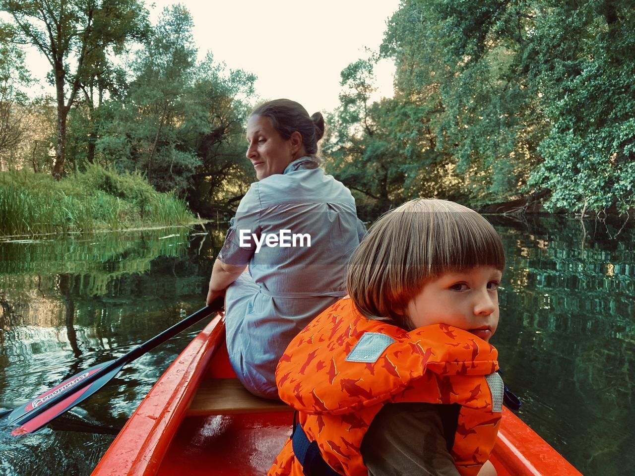 Boy looking at boat against trees