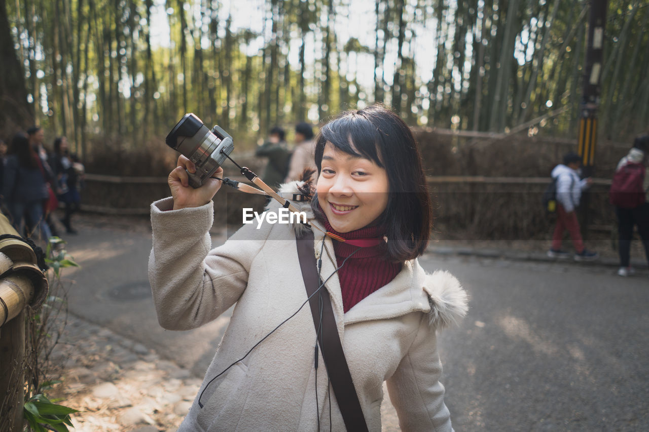 real people, portrait, looking at camera, tree, lifestyles, holding, focus on foreground, leisure activity, one person, standing, casual clothing, incidental people, nature, smiling, young adult, technology, plant, young women, outdoors, warm clothing