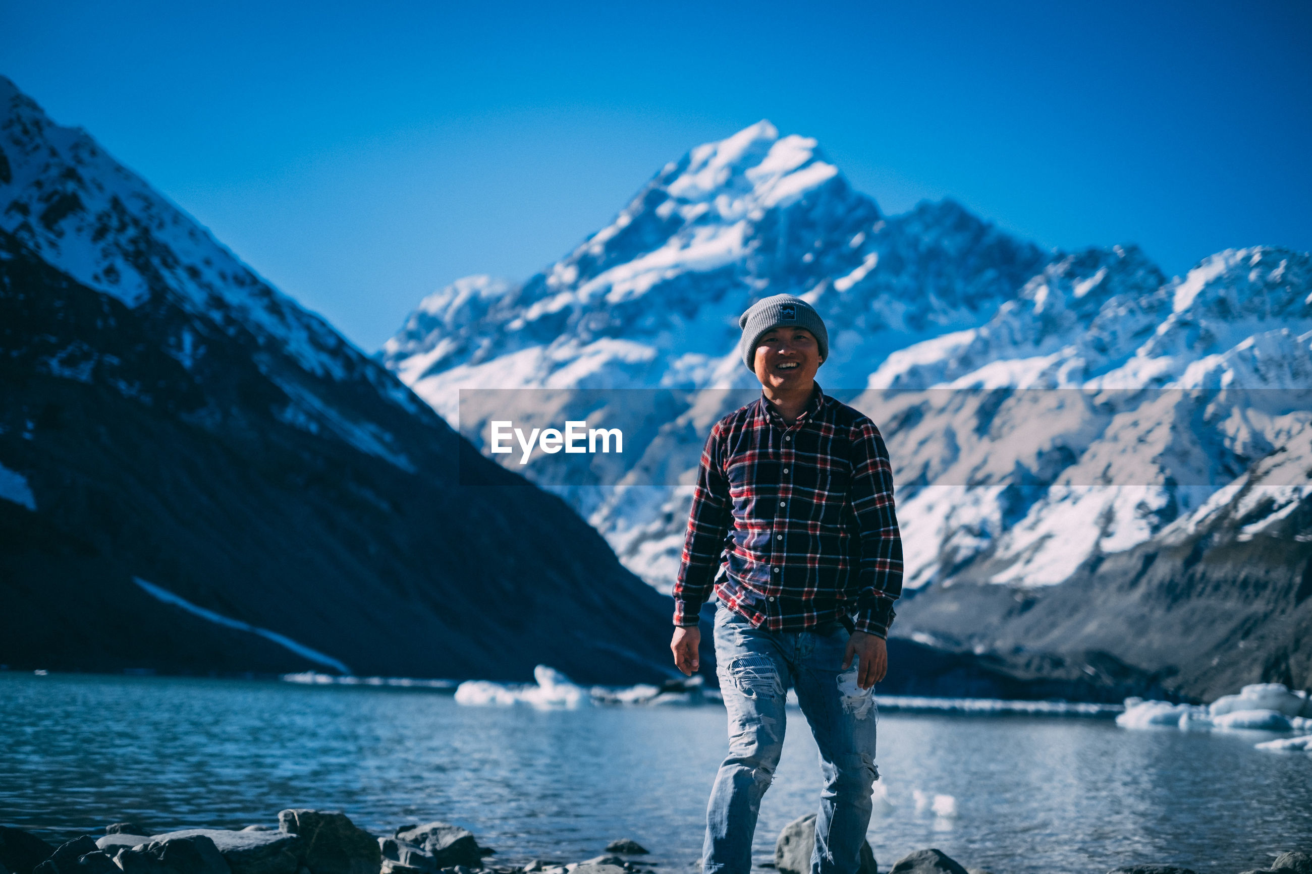 Portrait of man standing on snowcapped mountain against sky