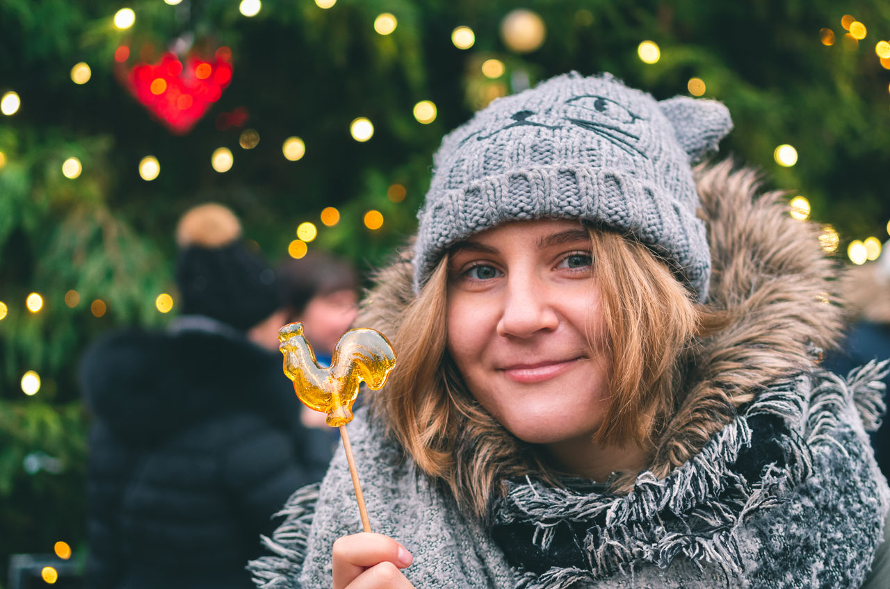 Portrait of smiling young woman holding candy against christmas tree