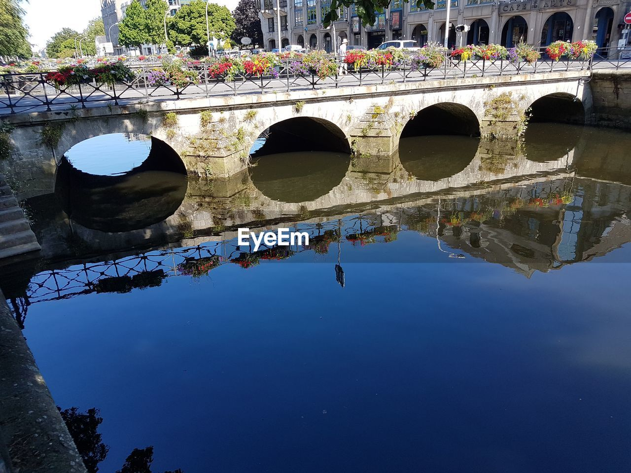 water, reflection, built structure, architecture, bridge, nature, arch, connection, bridge - man made structure, waterfront, day, arch bridge, river, building exterior, no people, transportation, sky, blue, outdoors, reflecting pool