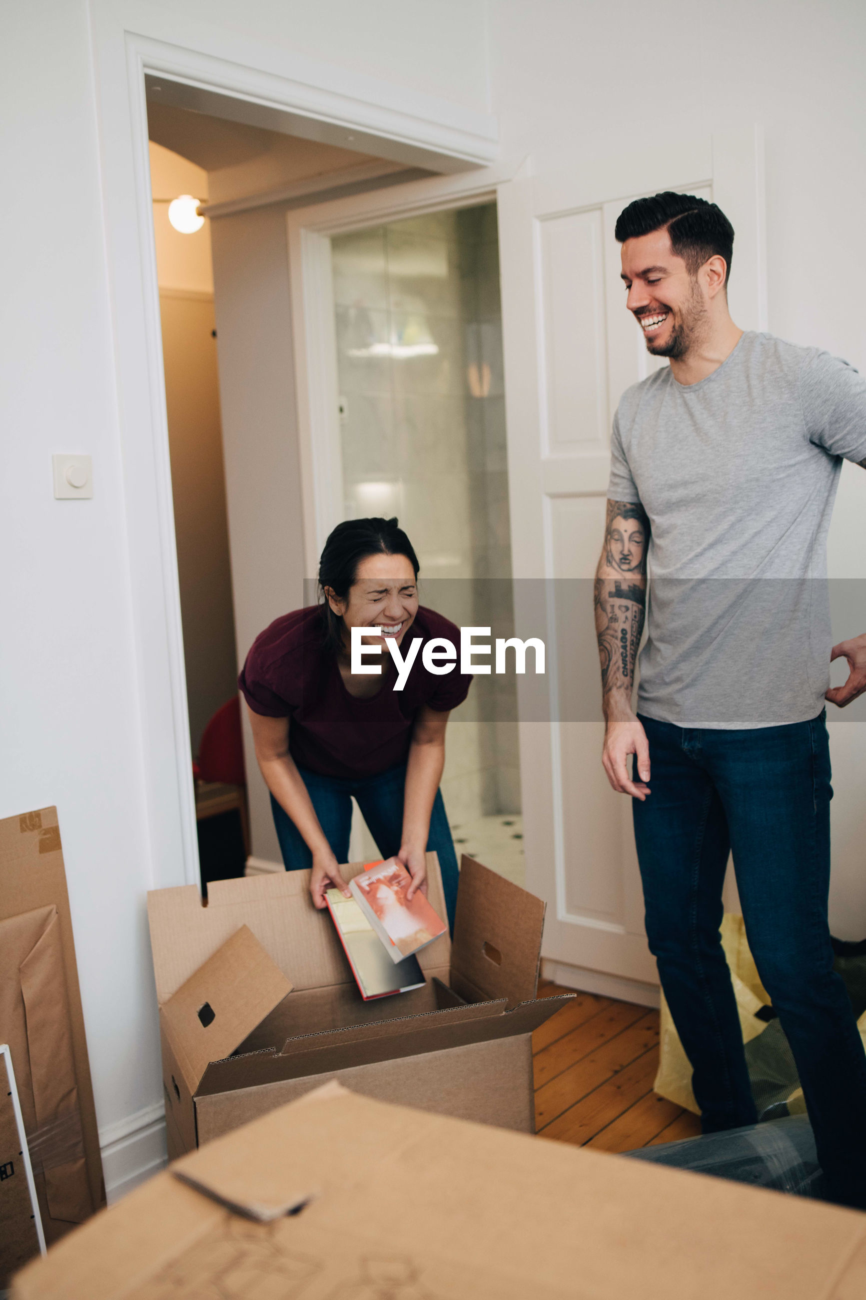 Couple enjoying while unpacking boxes in new apartment