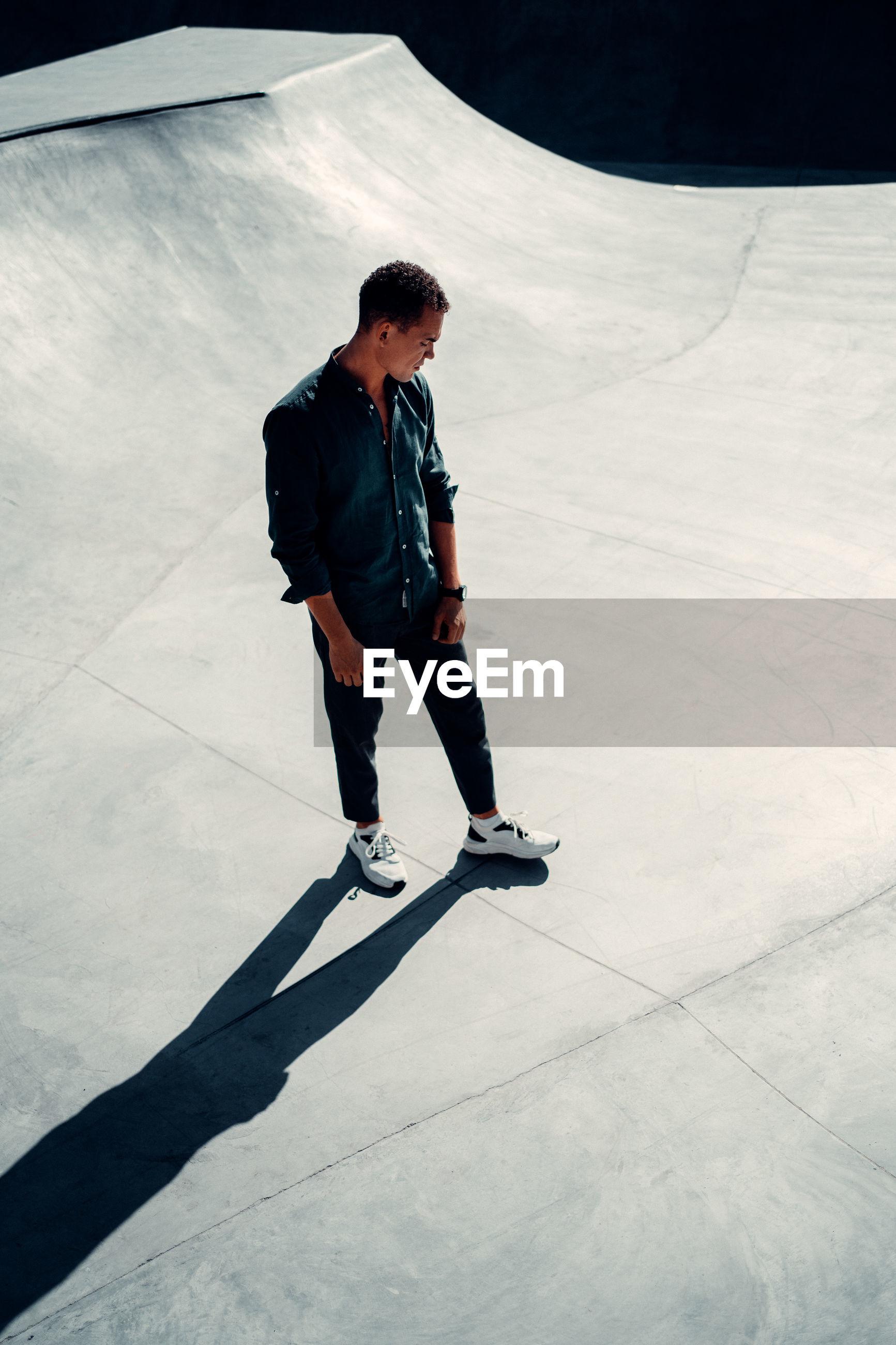 FULL LENGTH OF YOUNG MAN SKATEBOARDING ON SKATEBOARD