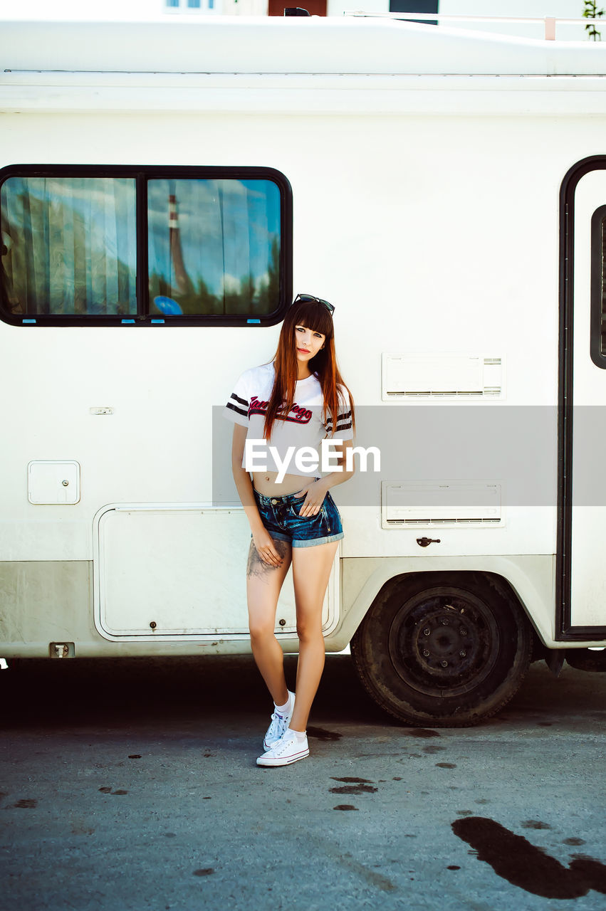 Full length portrait of young woman standing by camper trailer on street