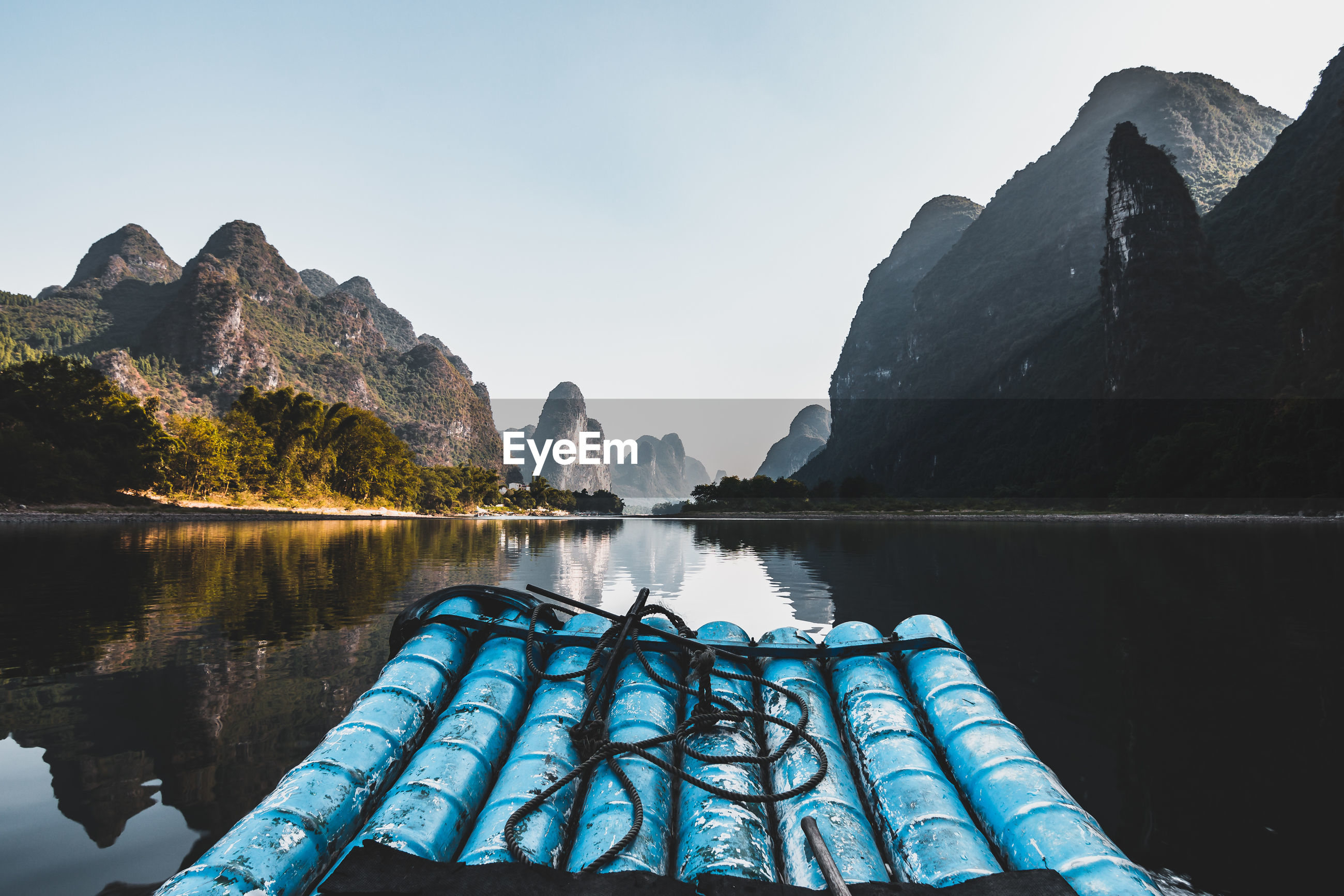 Blue wooden raft in lake with mountains in background against clear sky