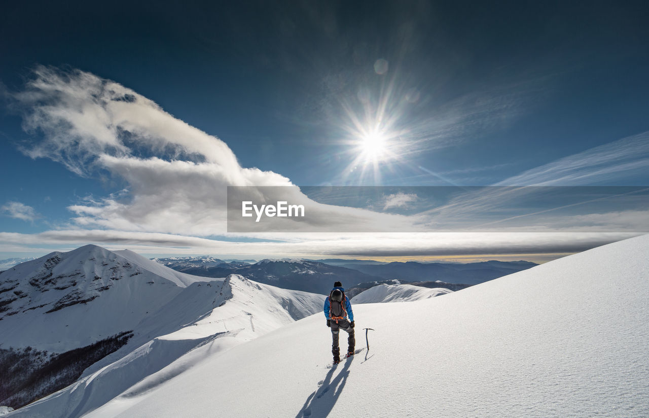 Rear View Of Mid Adult Man Hiking On Snowcapped Mountain Against Cloudy Sky